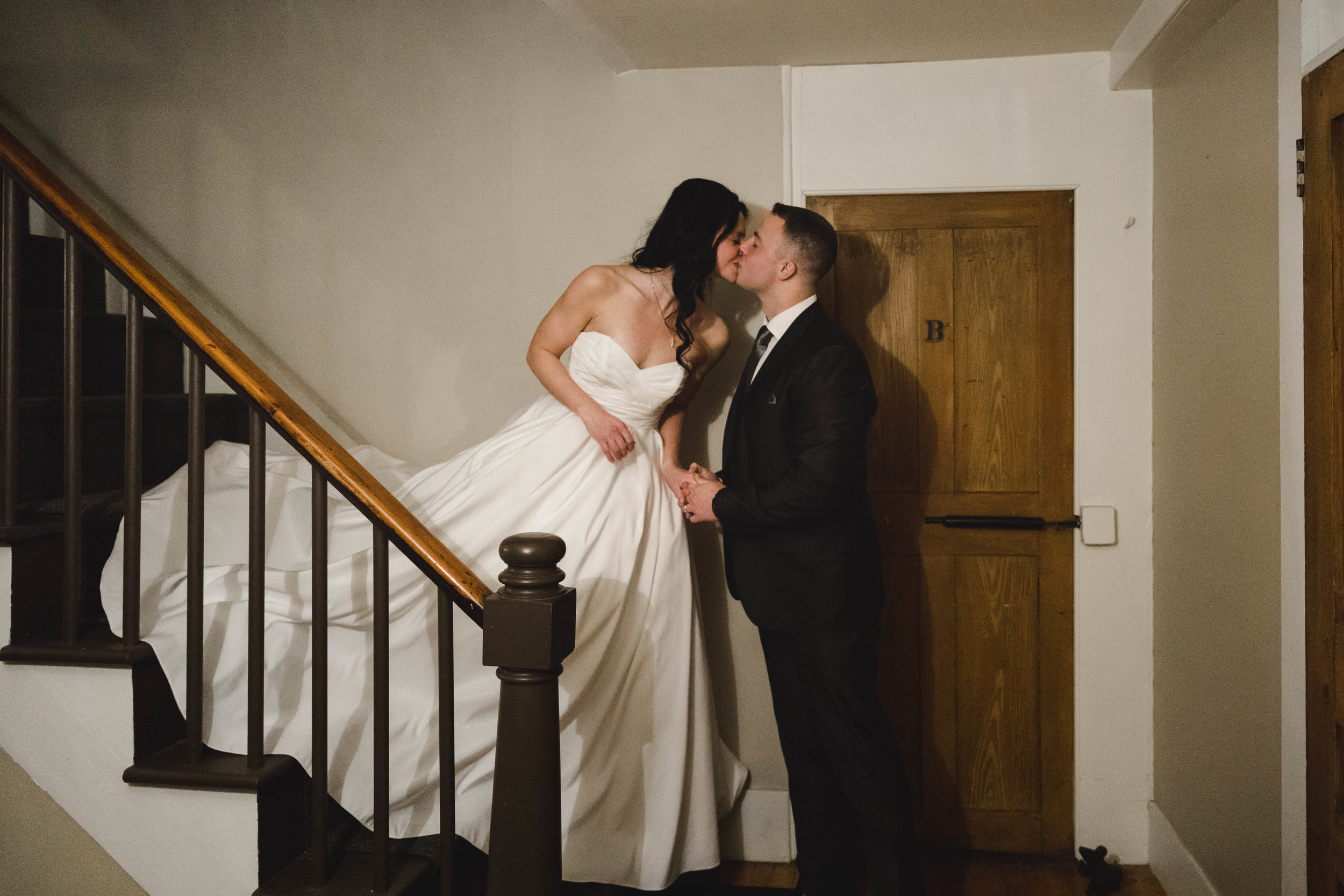 bride and groom kissing on stairs at Harrington farm