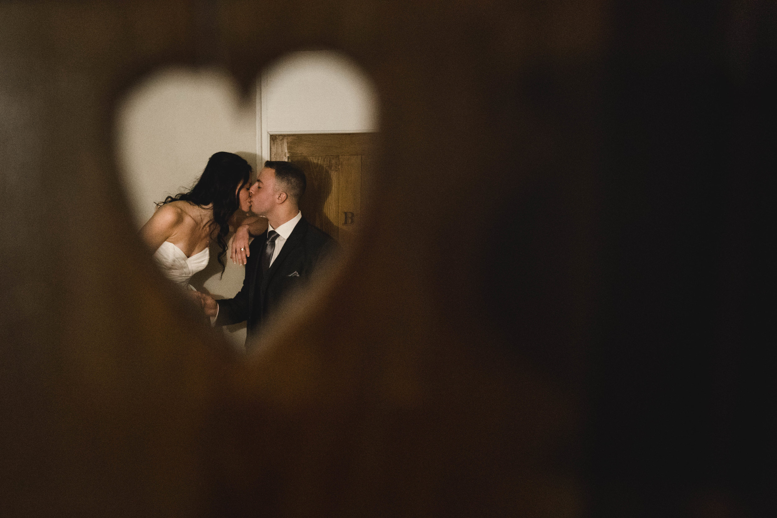 bride and groom kissing through heart shaped hole