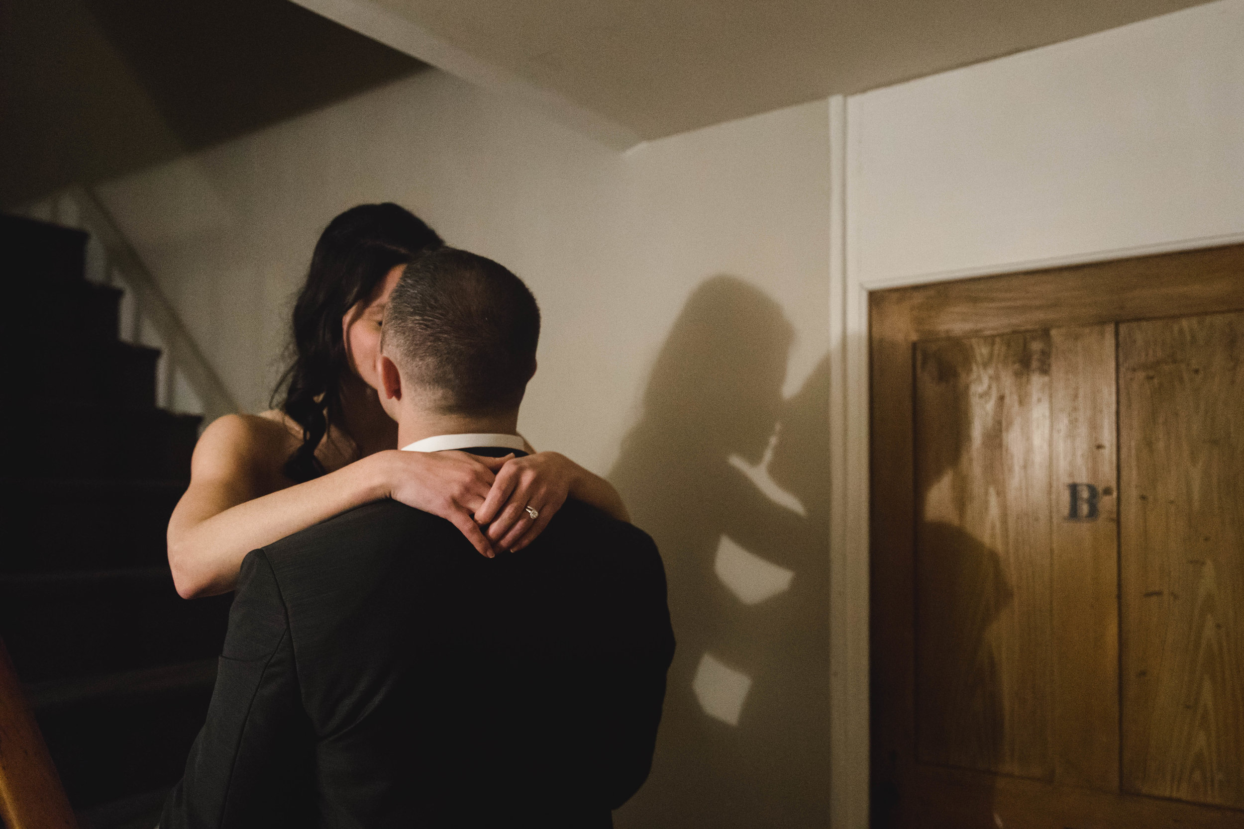 bride and groom kiss with shadow on wall