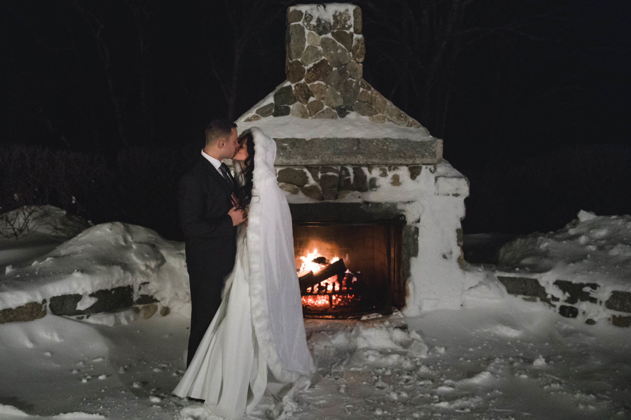 harrington farm outdoor fireplace at winter wedding with bride and groom