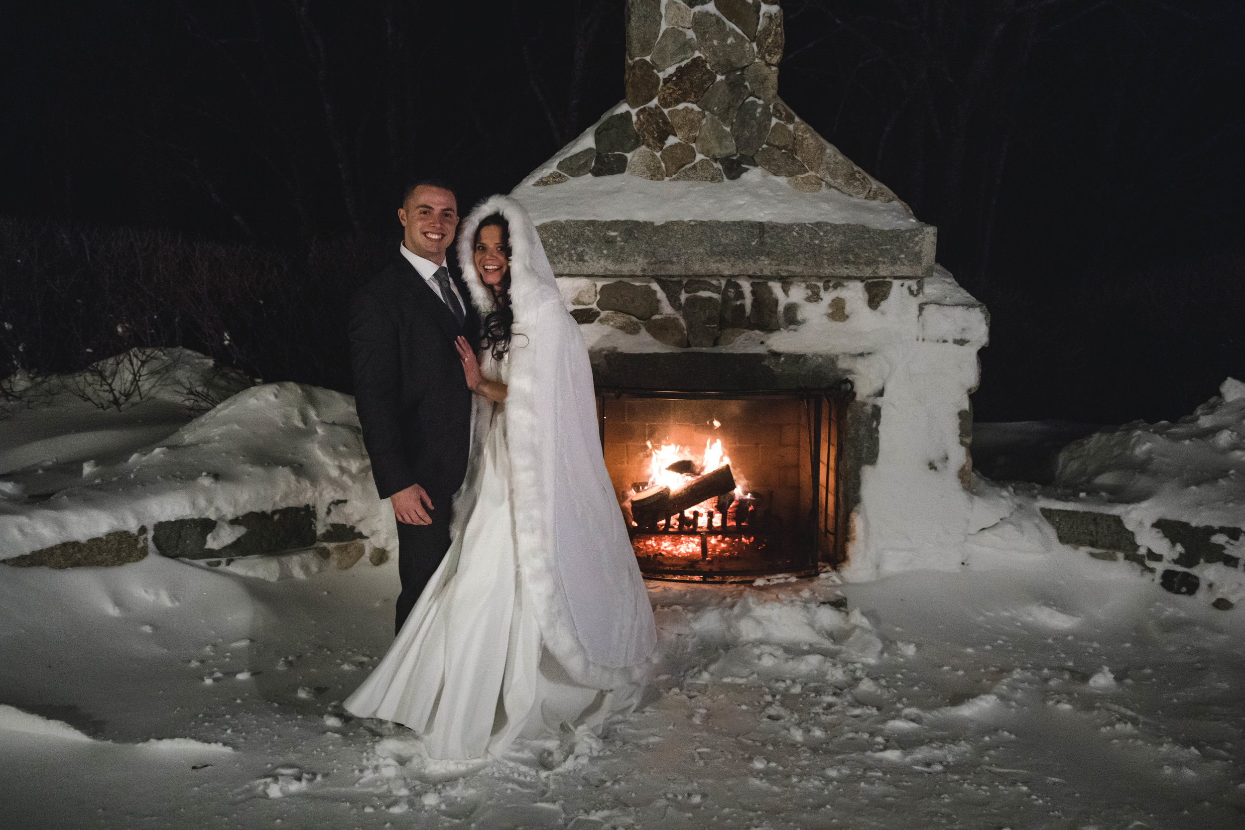 bride and groom at outdoor fireplace at Harrington Farm January wedding