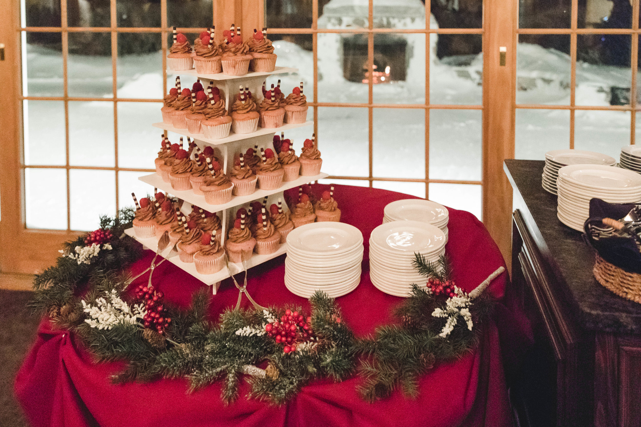wedding cupcake stand in front of outdoor fireplace January wedding