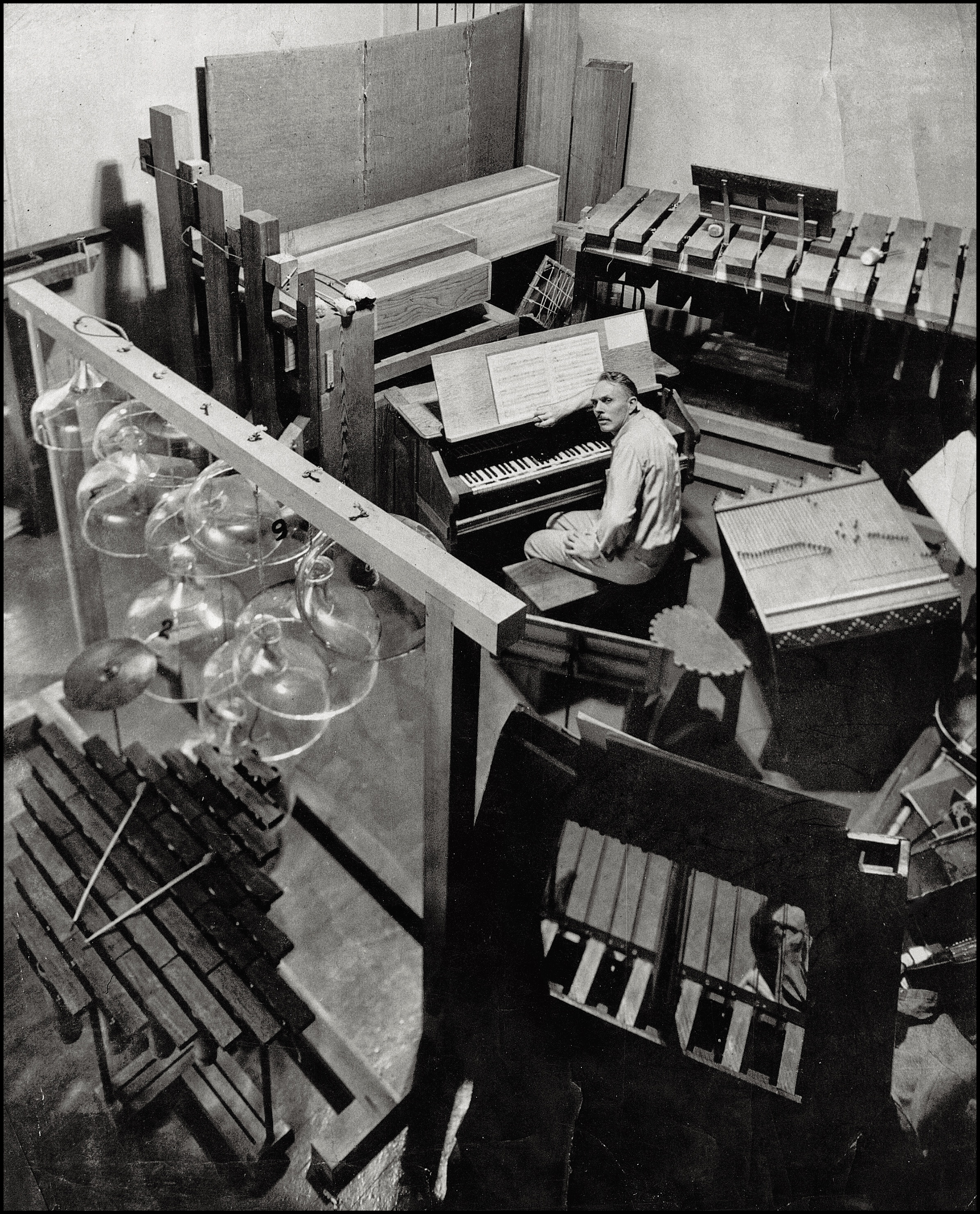 Partch in his studio, surrounded by his many instruments. Mills College, 1952