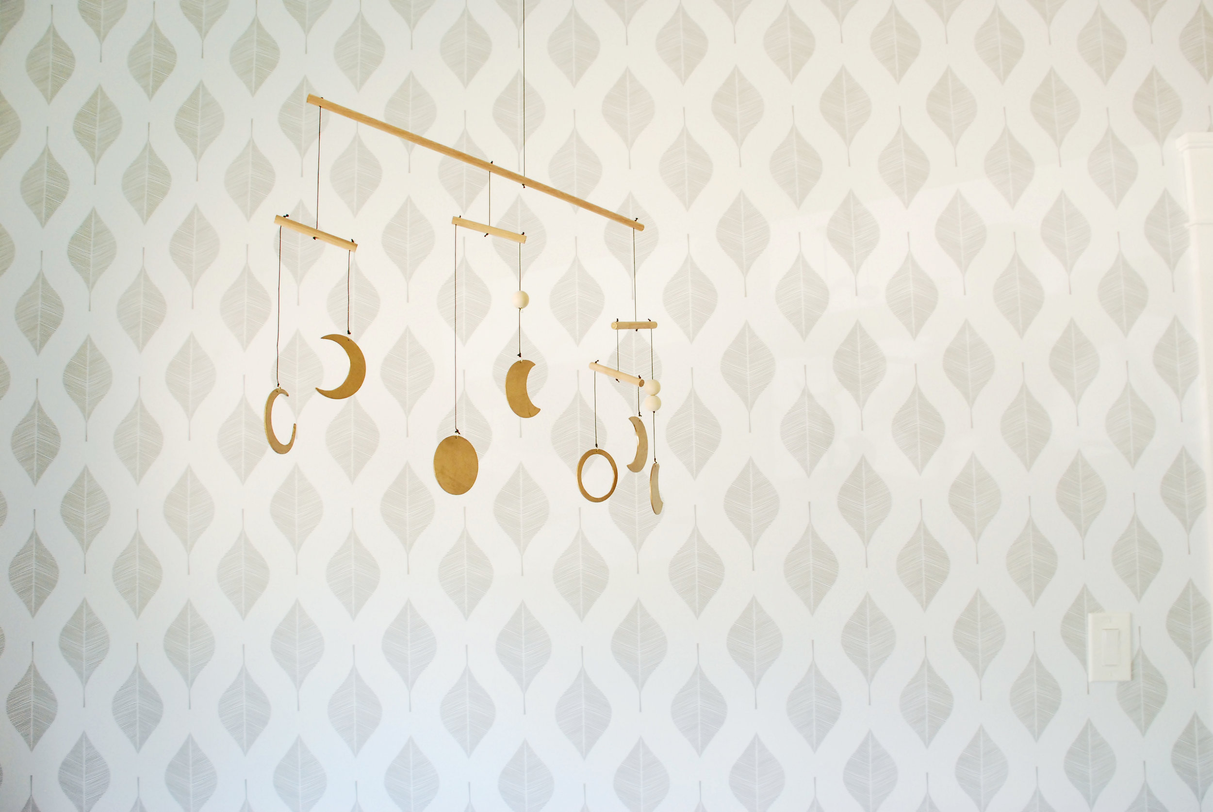 Wallpaper wall in baby nursery by Stay Interiors