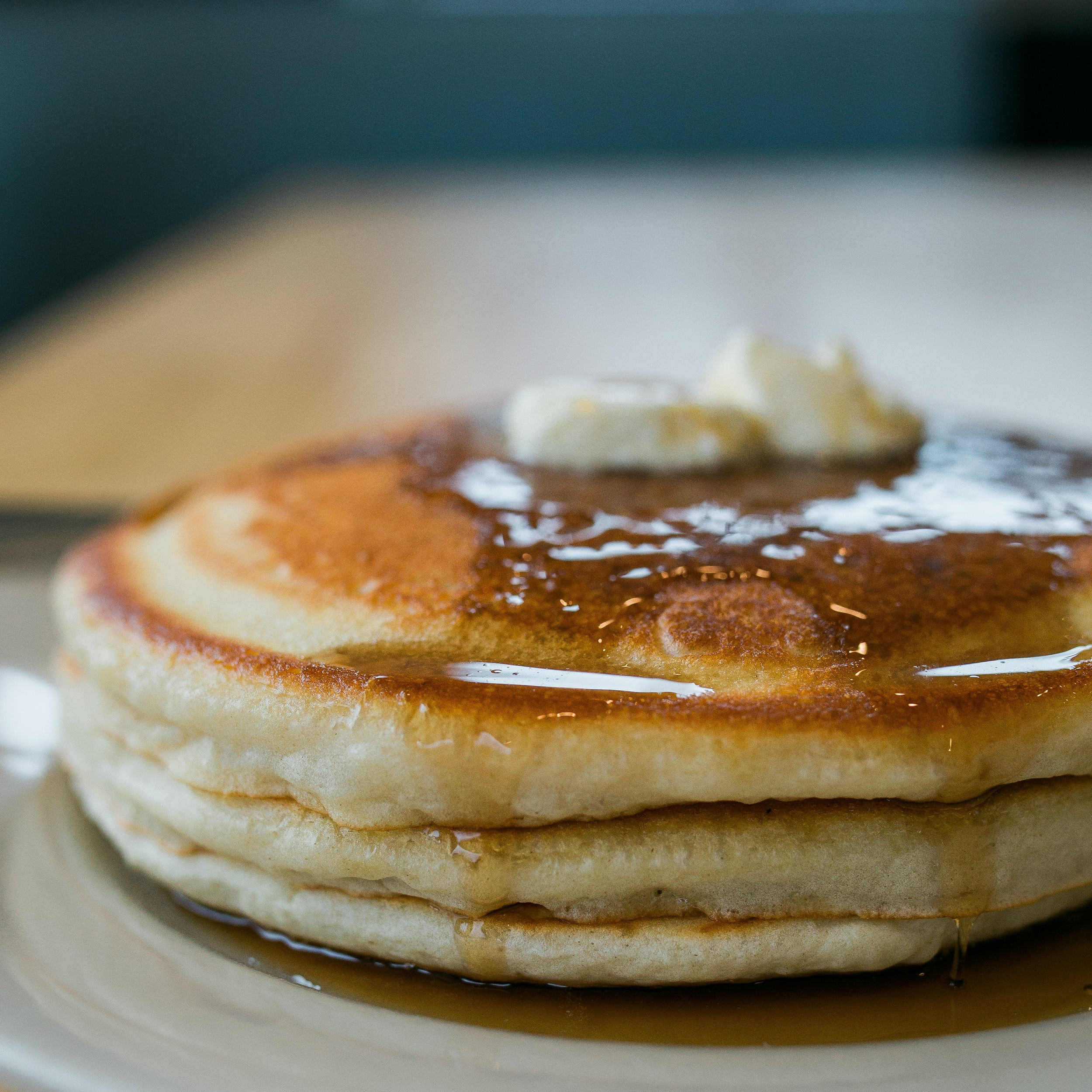stack of three buttermilk pancakes topped with butter pads and dripping with maple syrup