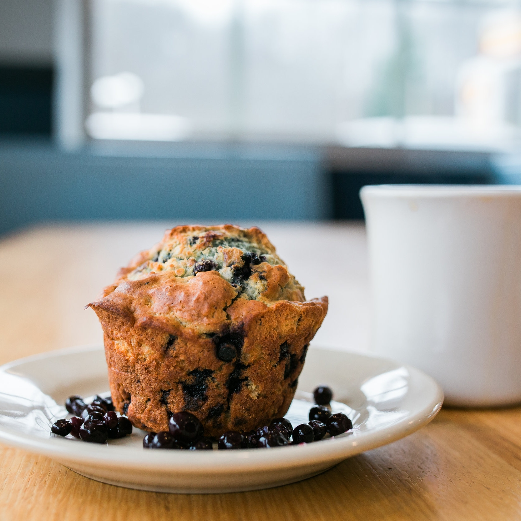 large blueberry muffin on a saucer surrounded by blueberries and next to a cup of coffee
