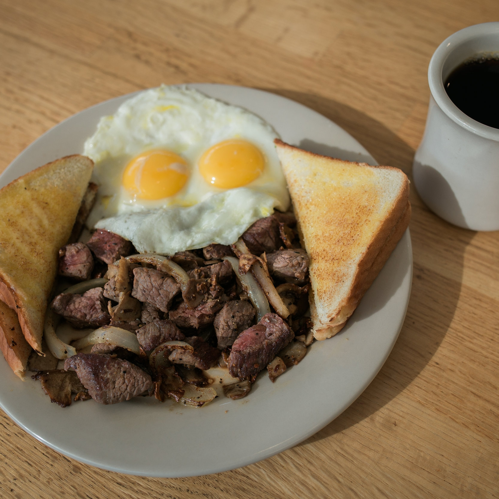 plate of beef tips with onions and peppers, a side of two over easy eggs, four triangles of buttered white toast, and a cup of black coffee