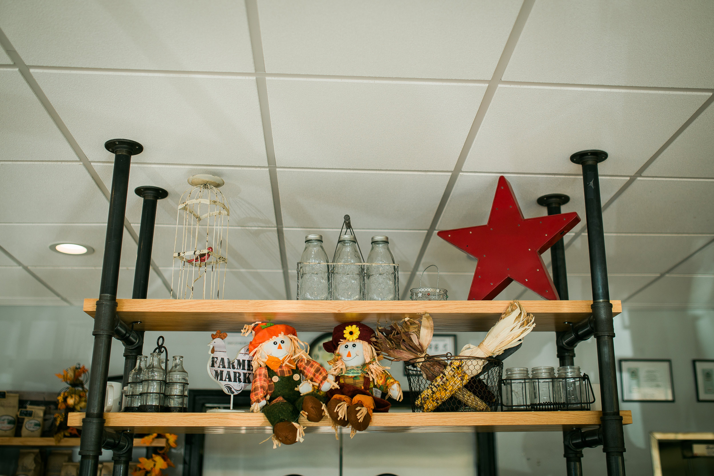 country farmhouse decor featuring red star and scarecrows as well as iron pipe shelving