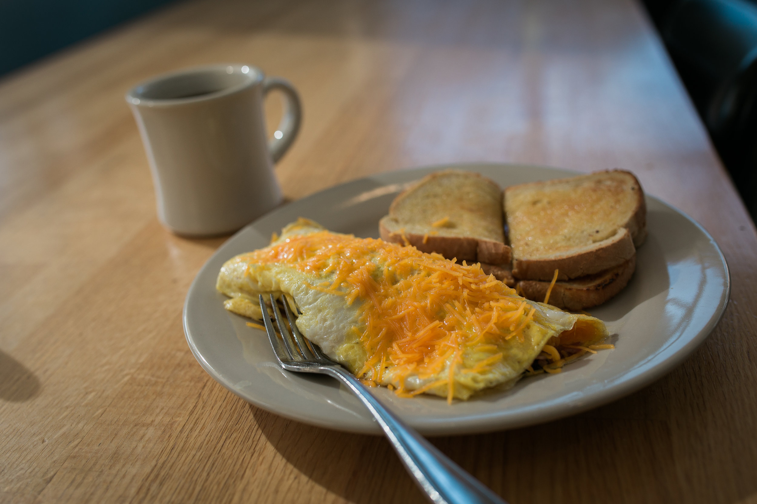 egg omelette smothered in shredded cheddar cheese, buttered wheat toast and a cup of coffee