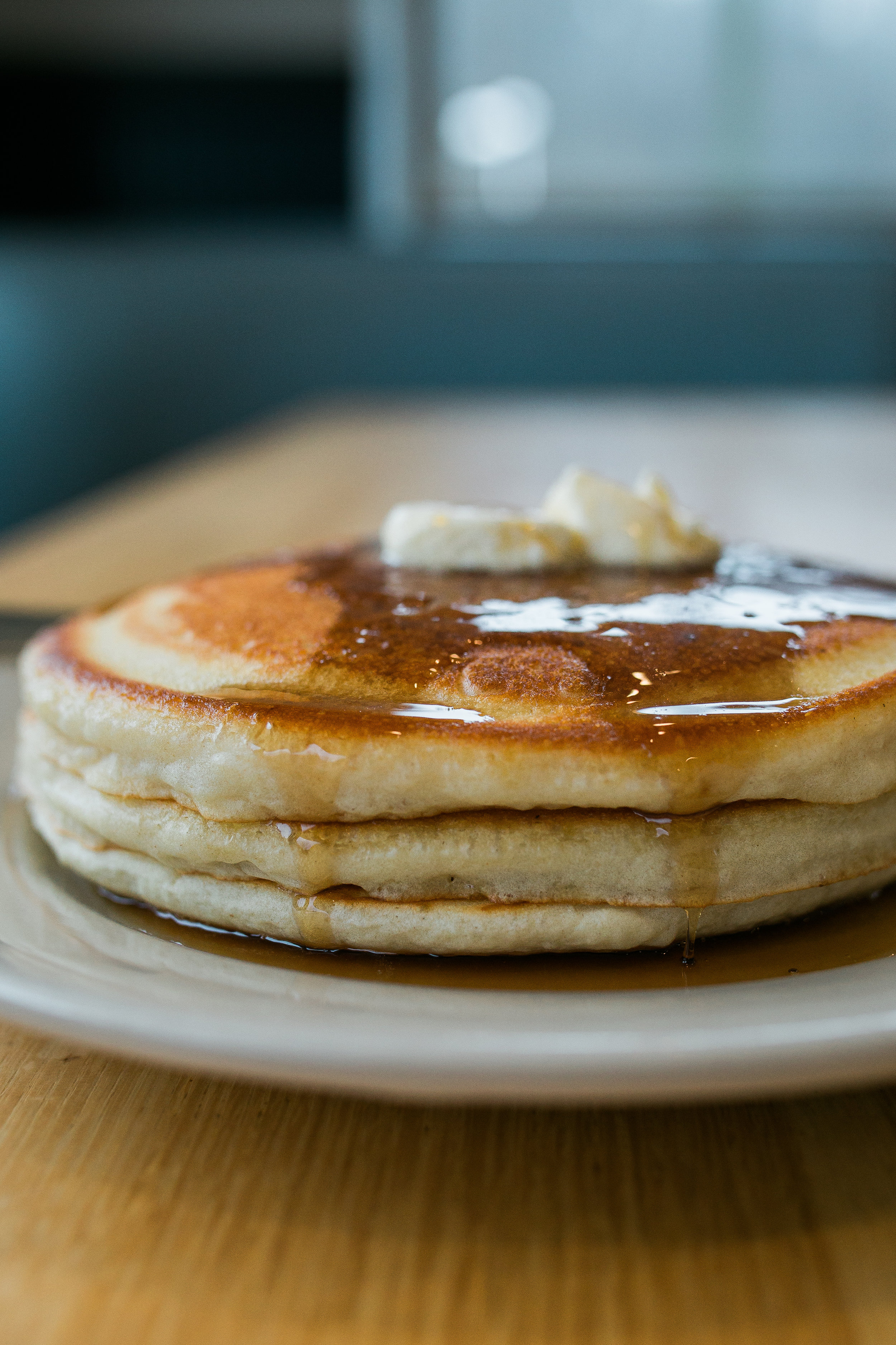 stack of three buttermilk pancakes with butter pads and maple syrup dripping down the sides