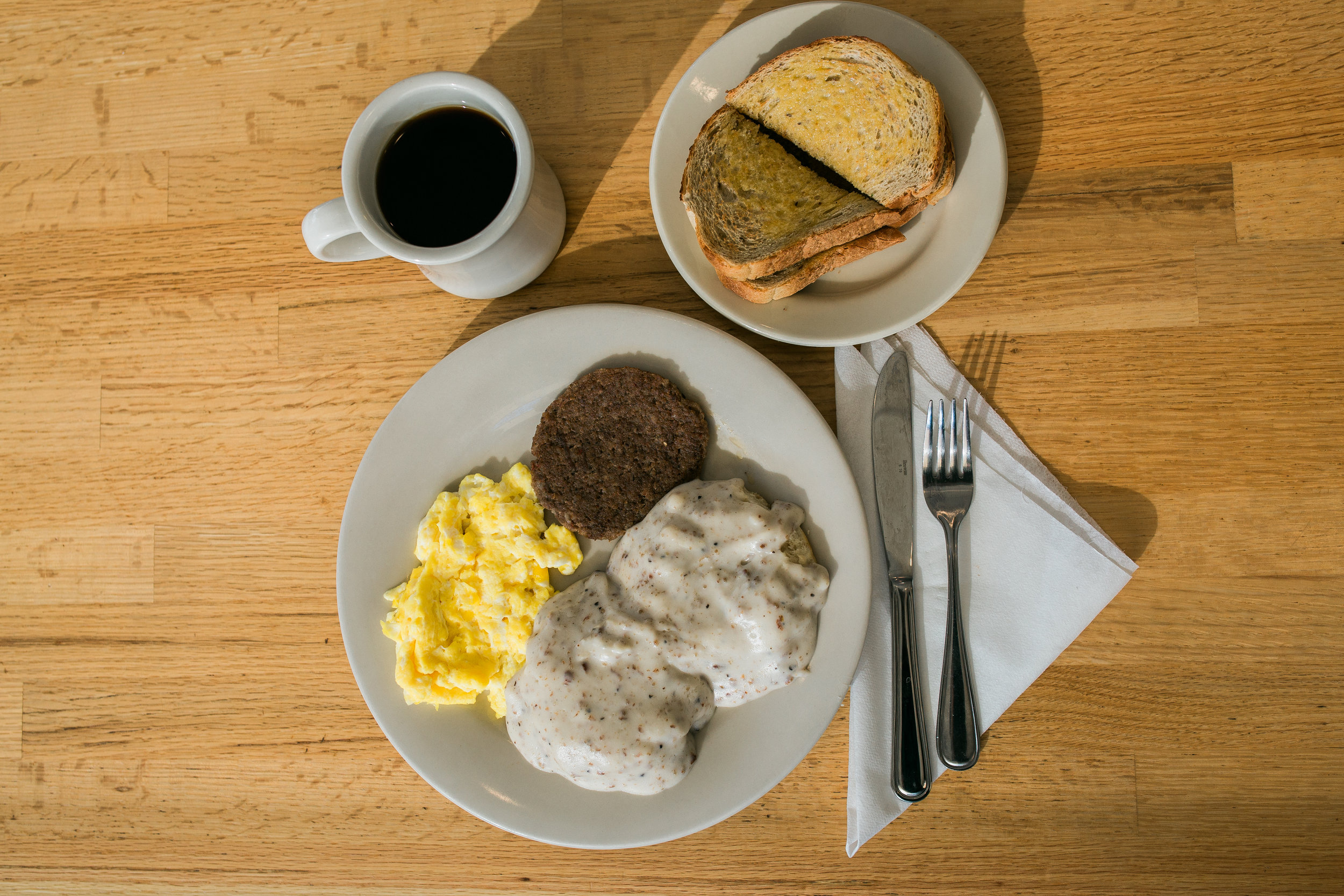 a hearty breakfast of two biscuits and country sausage gravy, scrambled eggs, a sausage patty, buttered rye toast and a cup of coffee