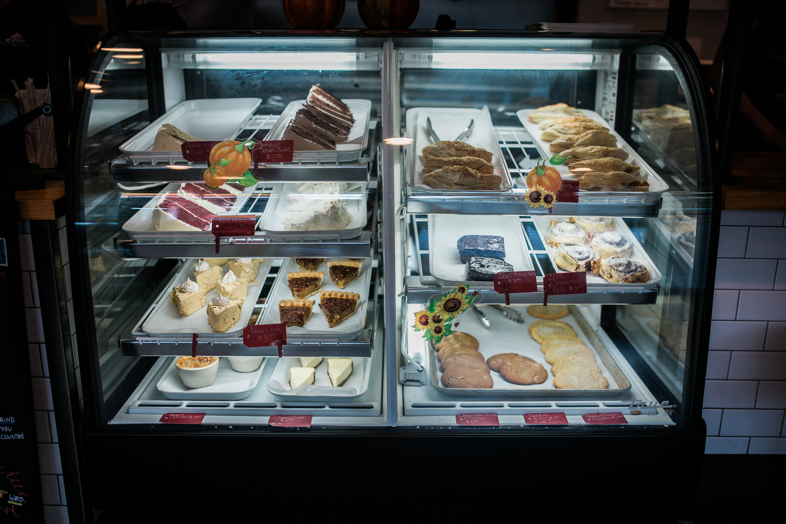 dessert display feauring pecan pie, red velvet cake, cookies, turnovers, and cheesecake