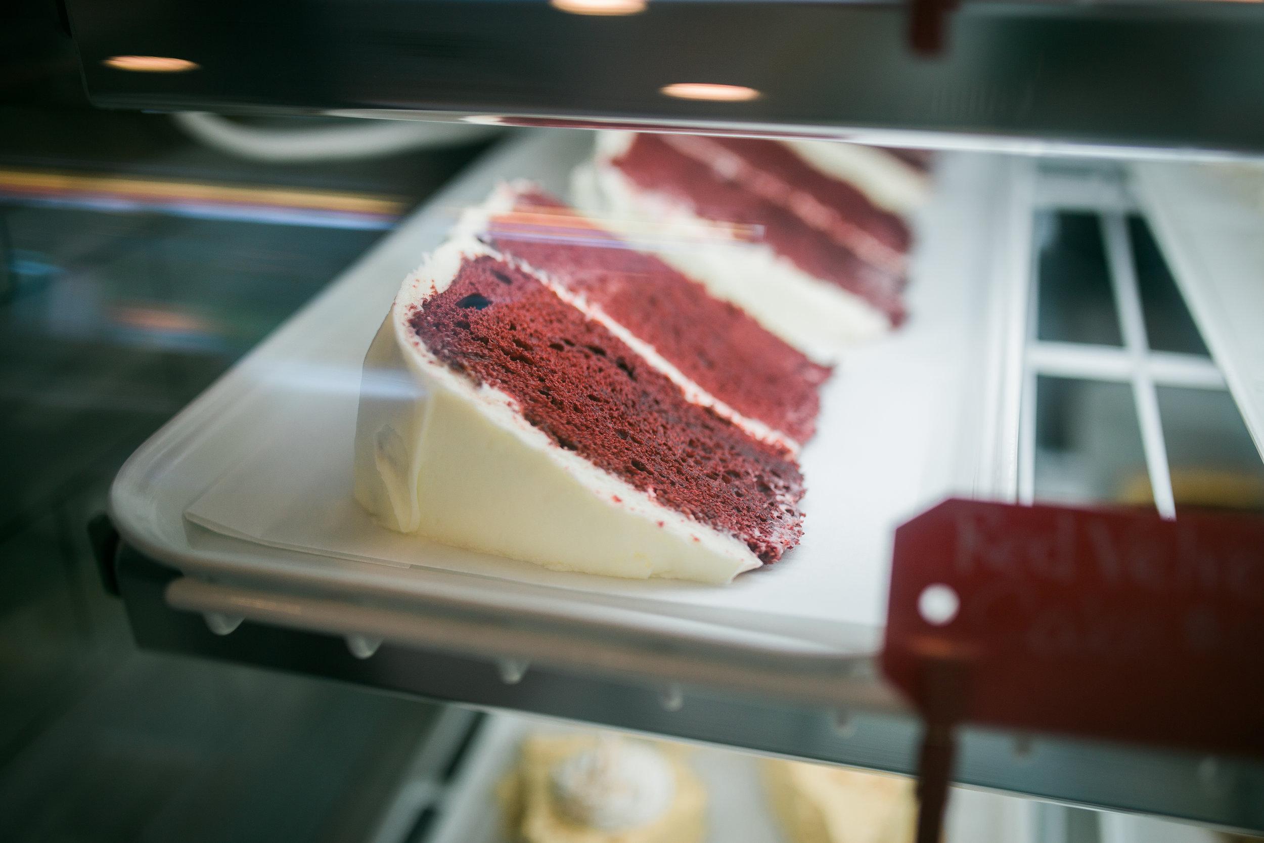 slices of red velvet cake inside a dessert display
