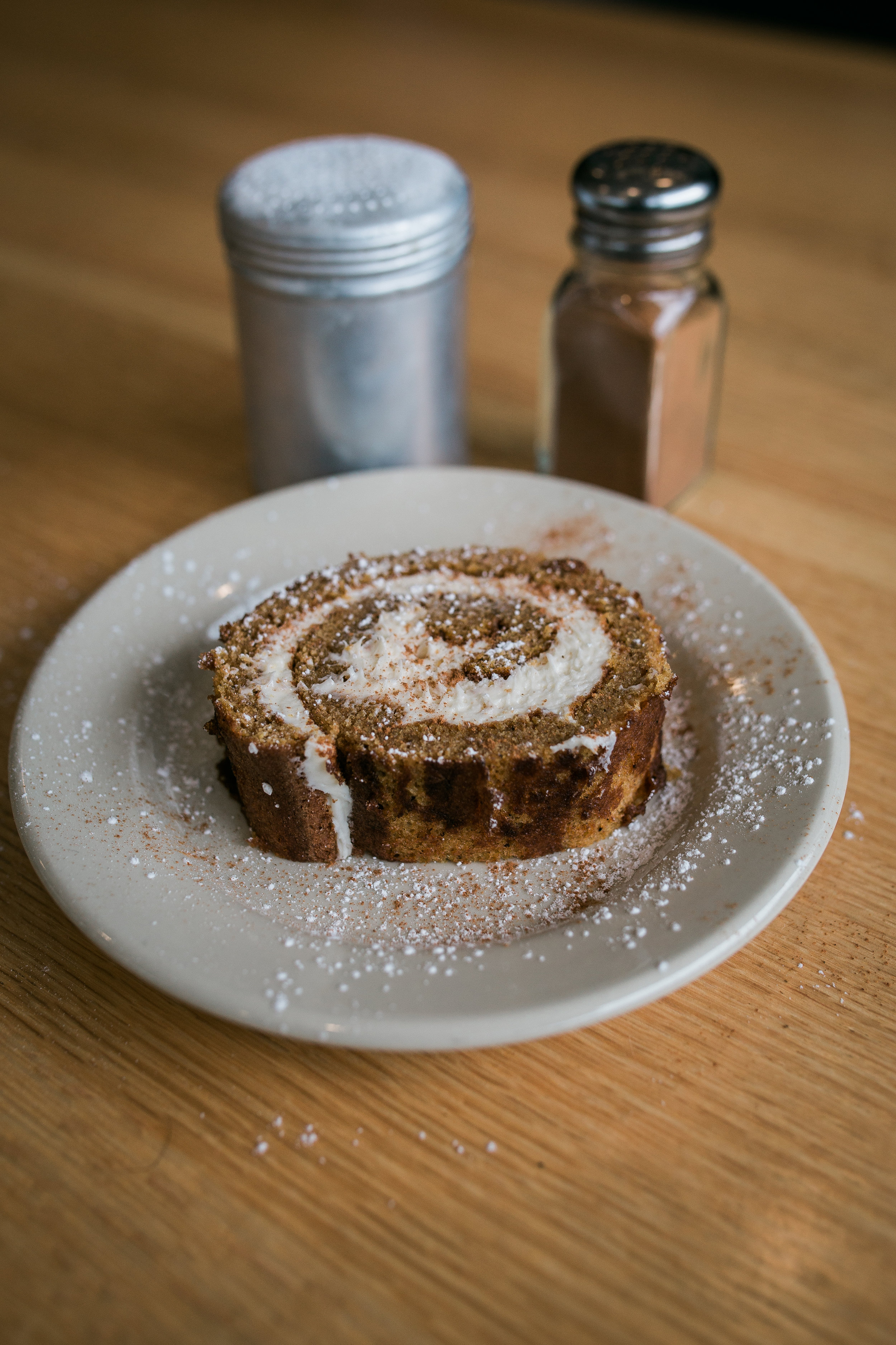 one pumpkin roll slice filled with cream cheese filling and sprinkled with powdered sugar and cinnamon