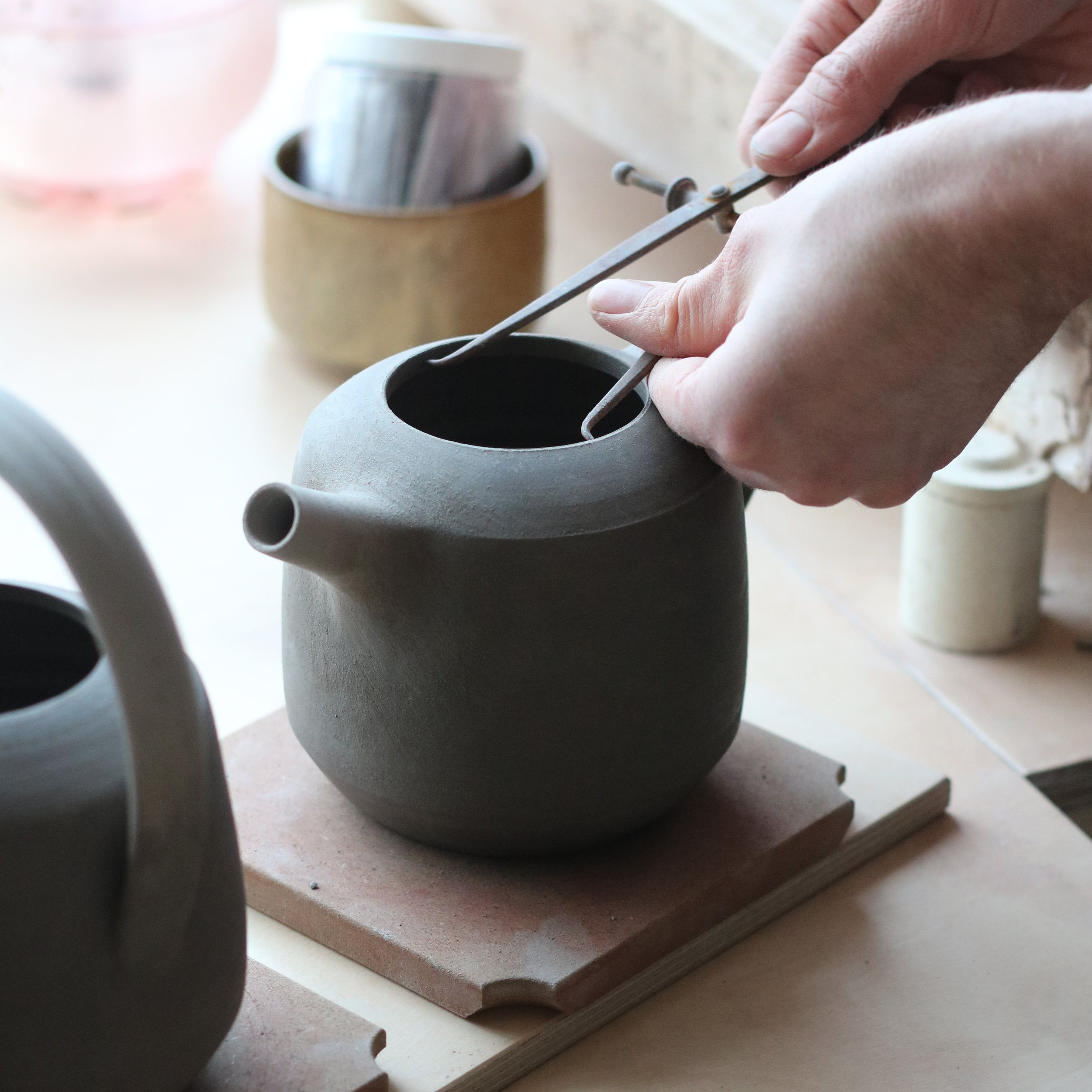 I'm learning about teapots at the moment. Can you talk about your lids and specifically fit? Do you have a locking mechanism, what type of gallery works best etc.? - We don't have a locking mechanism for our lids and we use an open gallery with a flanged lid that sits on top and outside. We do ours in batches so all the lids and holes are the correct size (as opposed to one lid per one teapot).