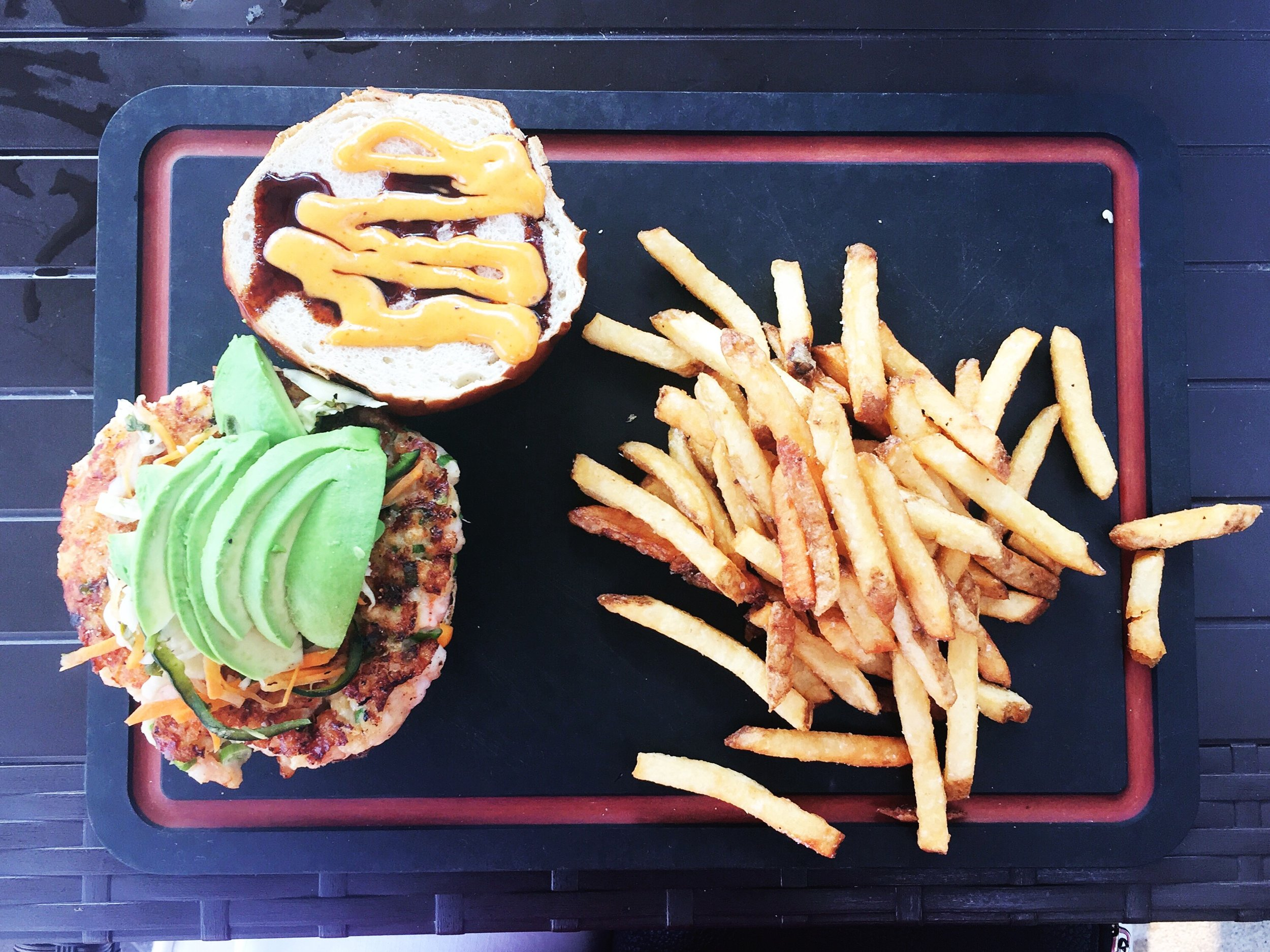 Shrimp burger with pepper slaw, avocado, sriracha aioli, unagi sauce.