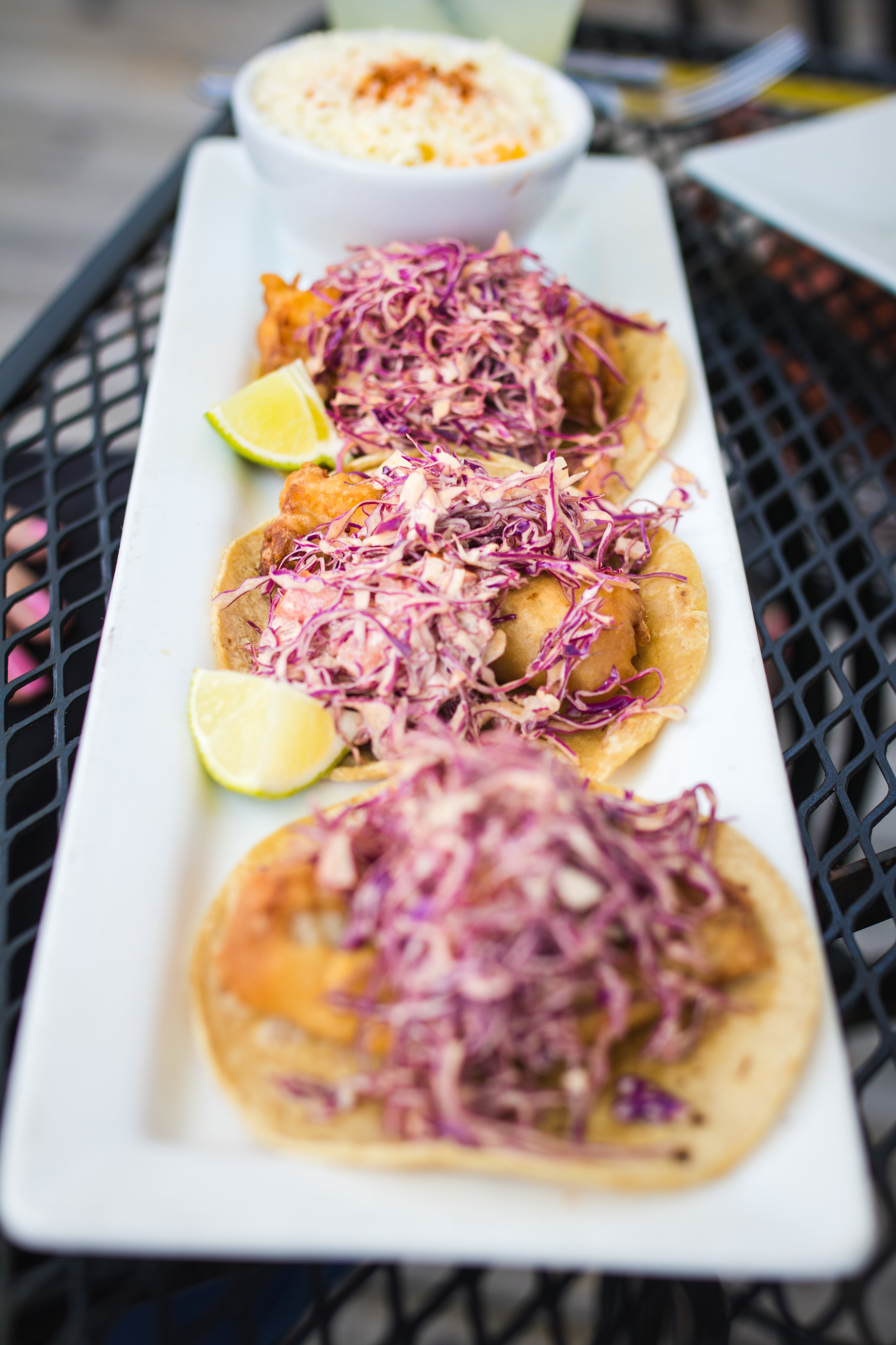 Cabos tacos: beer battered fried fish on soft corn tortillas with red cabbage slaw and chipotle aioli.