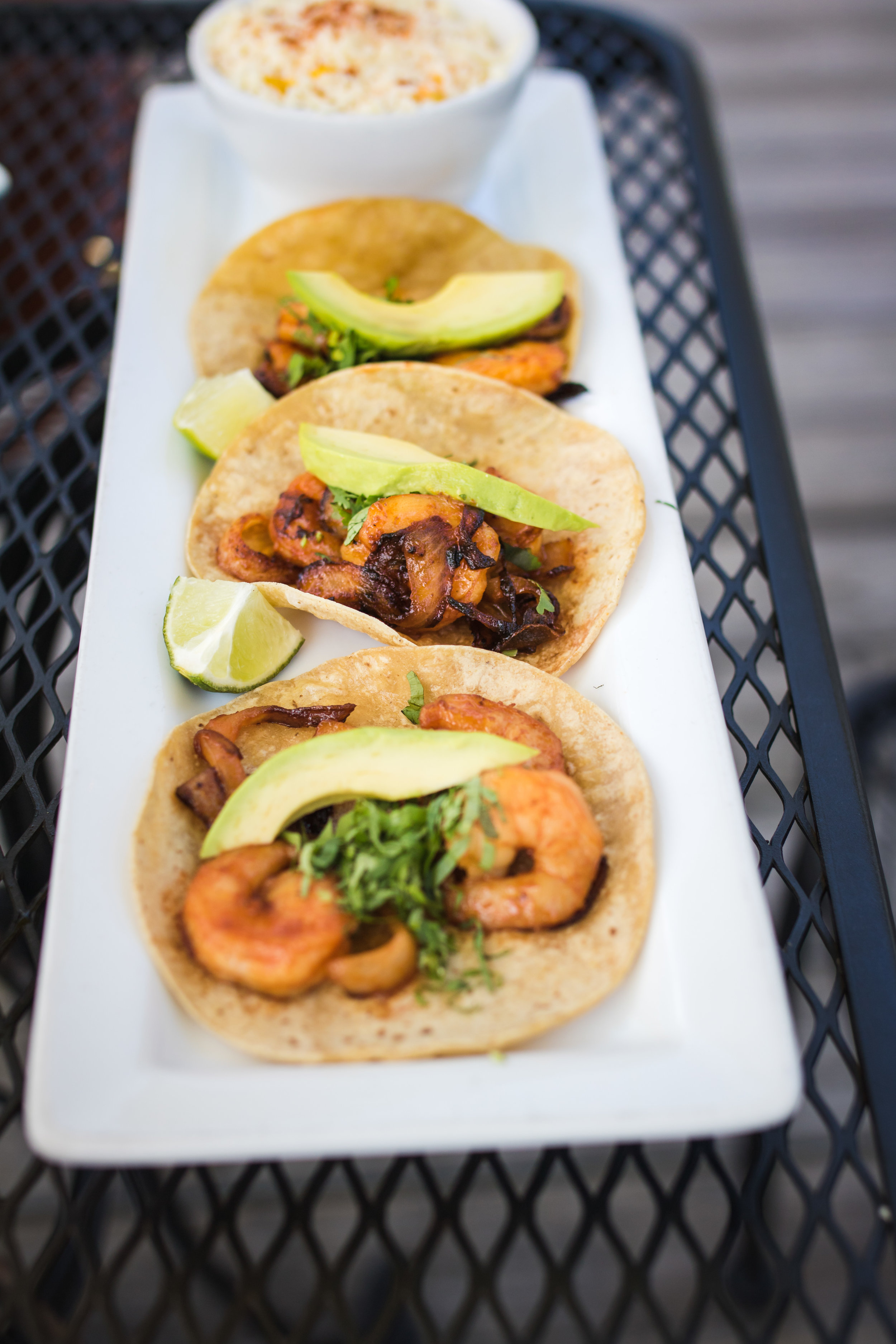 Camaron tacos with sauteed shrimp with grilled onions in chipotle sauce topped with cilantro and sliced avocado.