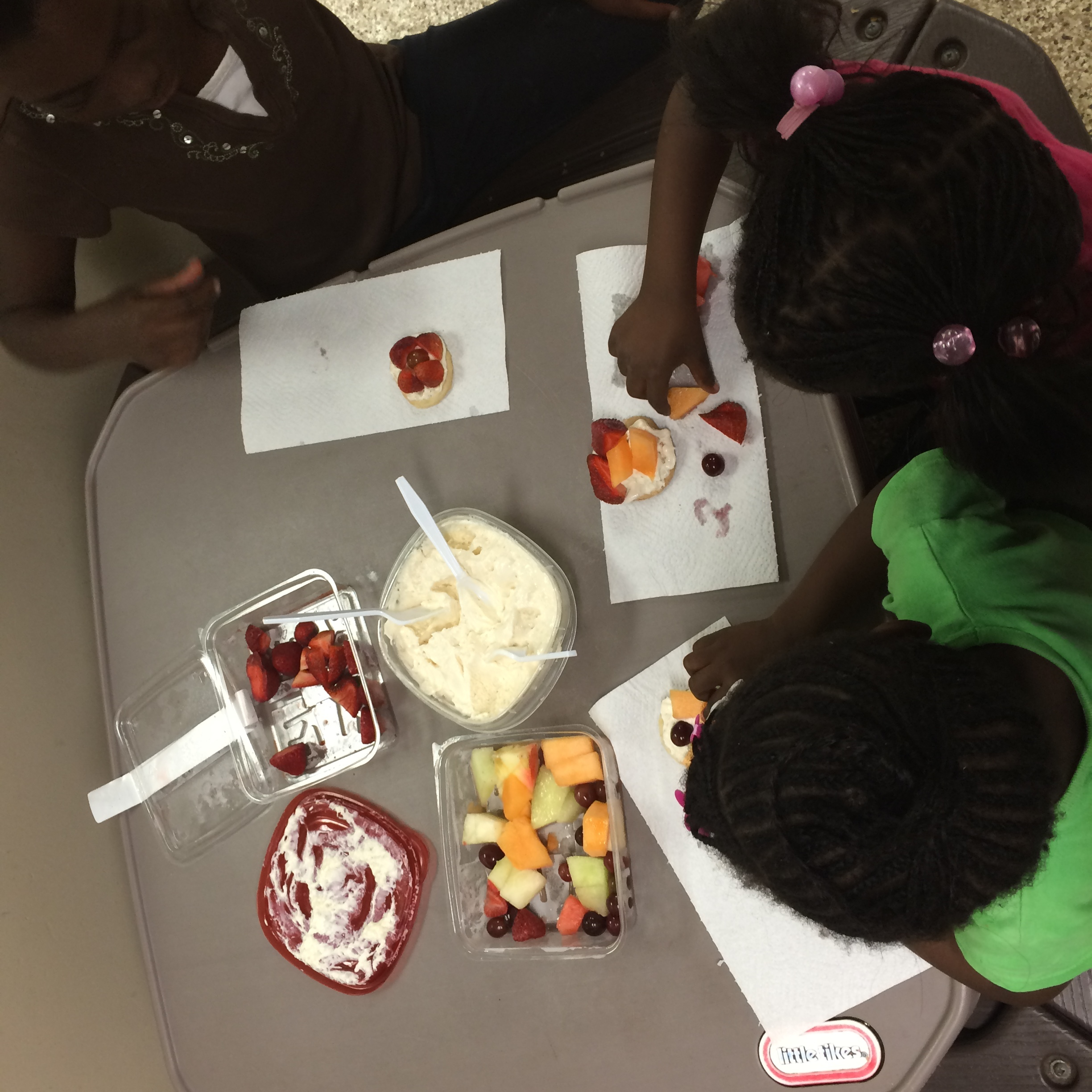 Children make fruit pizzas at the Farm to Table Fun station at Central Pantry.