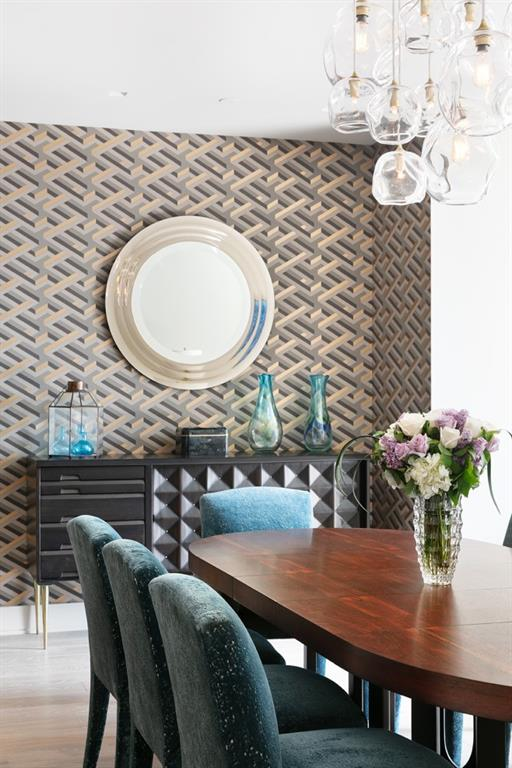 The rich graphic wallpaper sets the tone for this space.  The vintage sideboard on stiletto brass legs pops off the light oak floors.