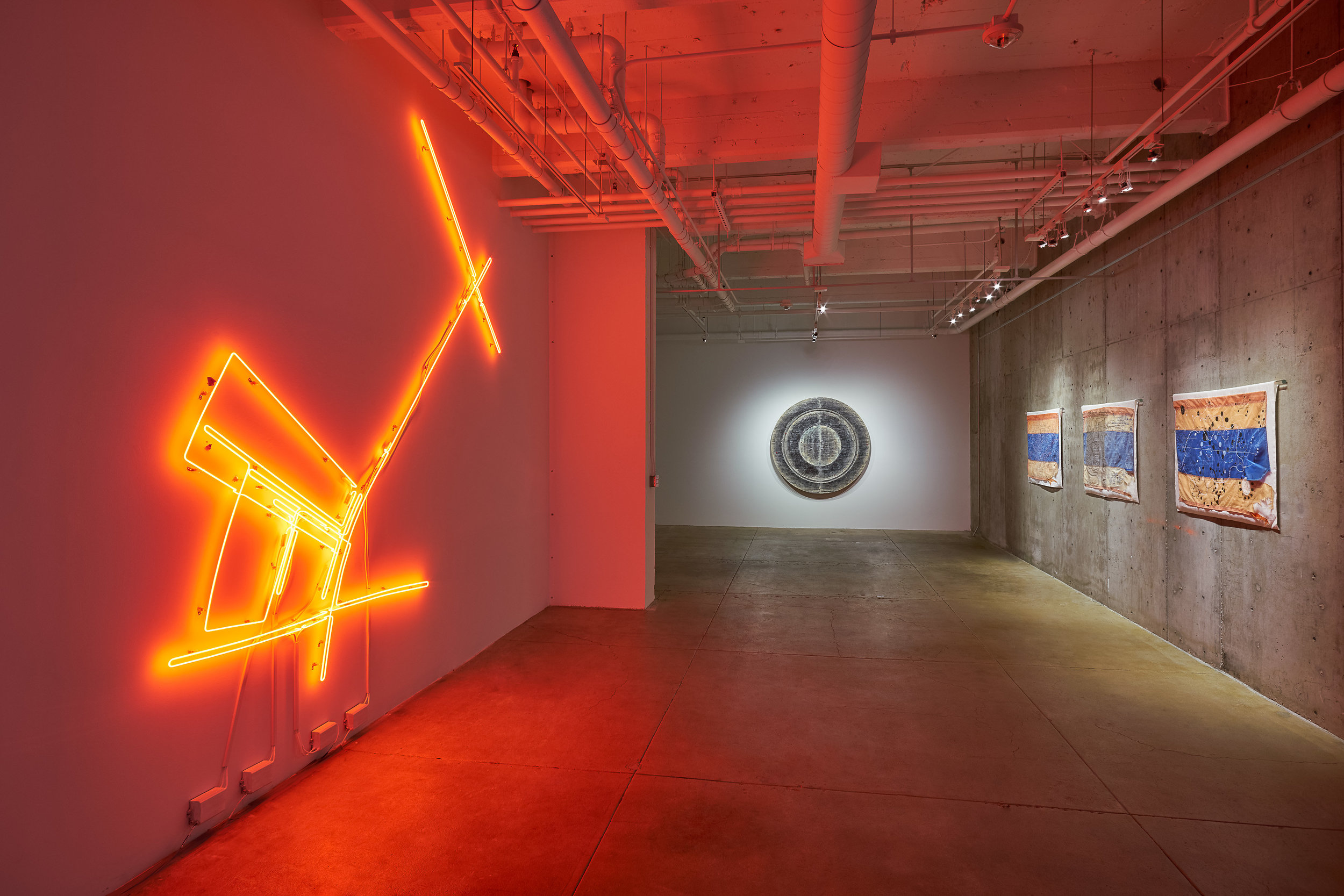 Exhibition documentation of Omar Mismar  The Path of Love #03 , 2013-2014, neon, 126 x 126 inches (left), Taraneh Hemami  Recounting , 2011, pigment and inkjet prints on paper and vellum, wax, wood panels, 66 inches diameter, 7 inches deep (center) and Guillermo Galindo Siguiendo  Los Pasos del Niño Perdido, 20 Miles East of Laredo , and  Cartografía del Espiritu/Cartography of the Spirit,  all 2017, acrylic on beacon flags used by humanitarian aid group Water Stations (right). Image courtesy of the artists and Gallery Wendi Norris, San Francisco.