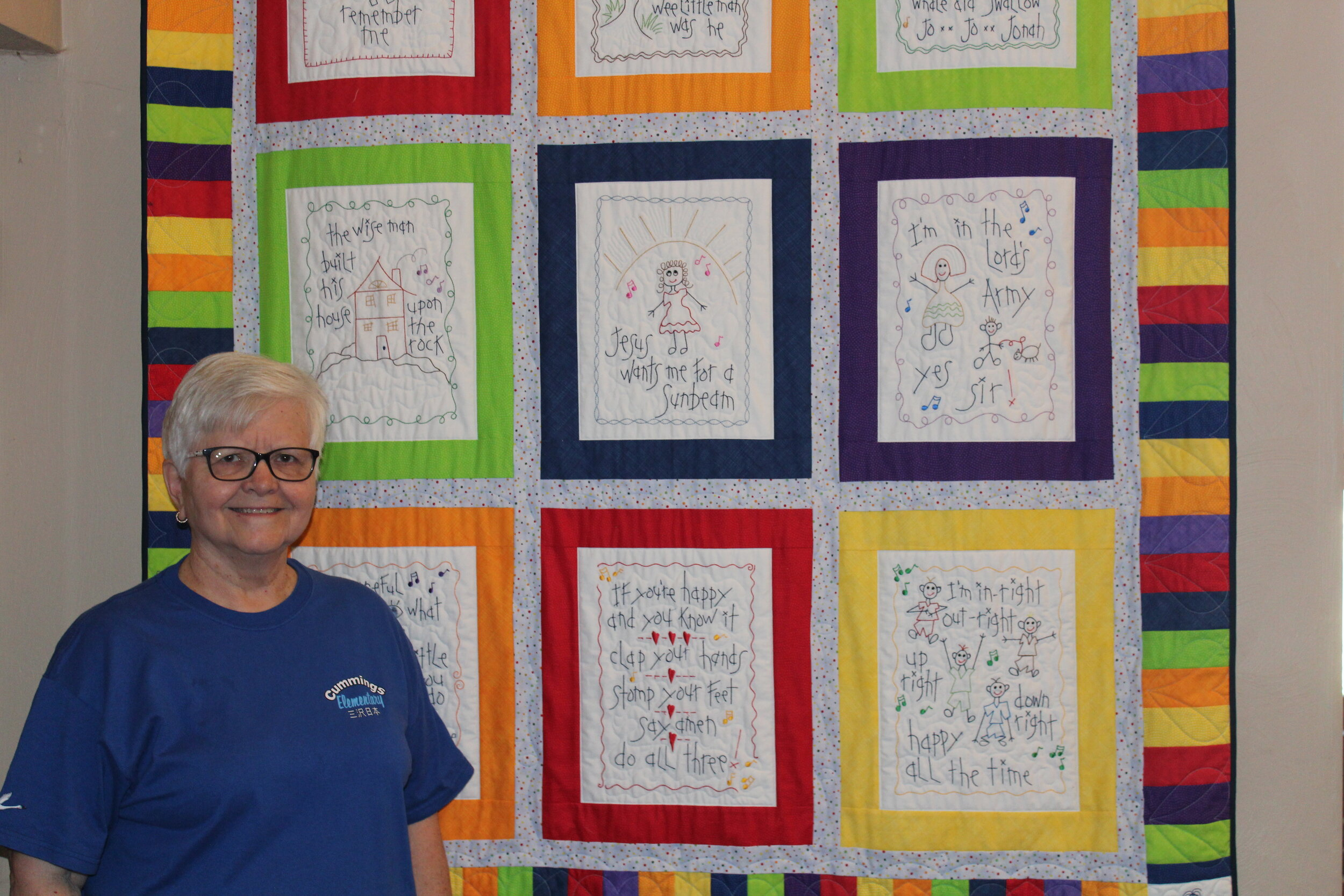 Louise Warner stands next to a quilt that hangs in the Fellowship Hall and was created by Dutilh's MHY quilters.