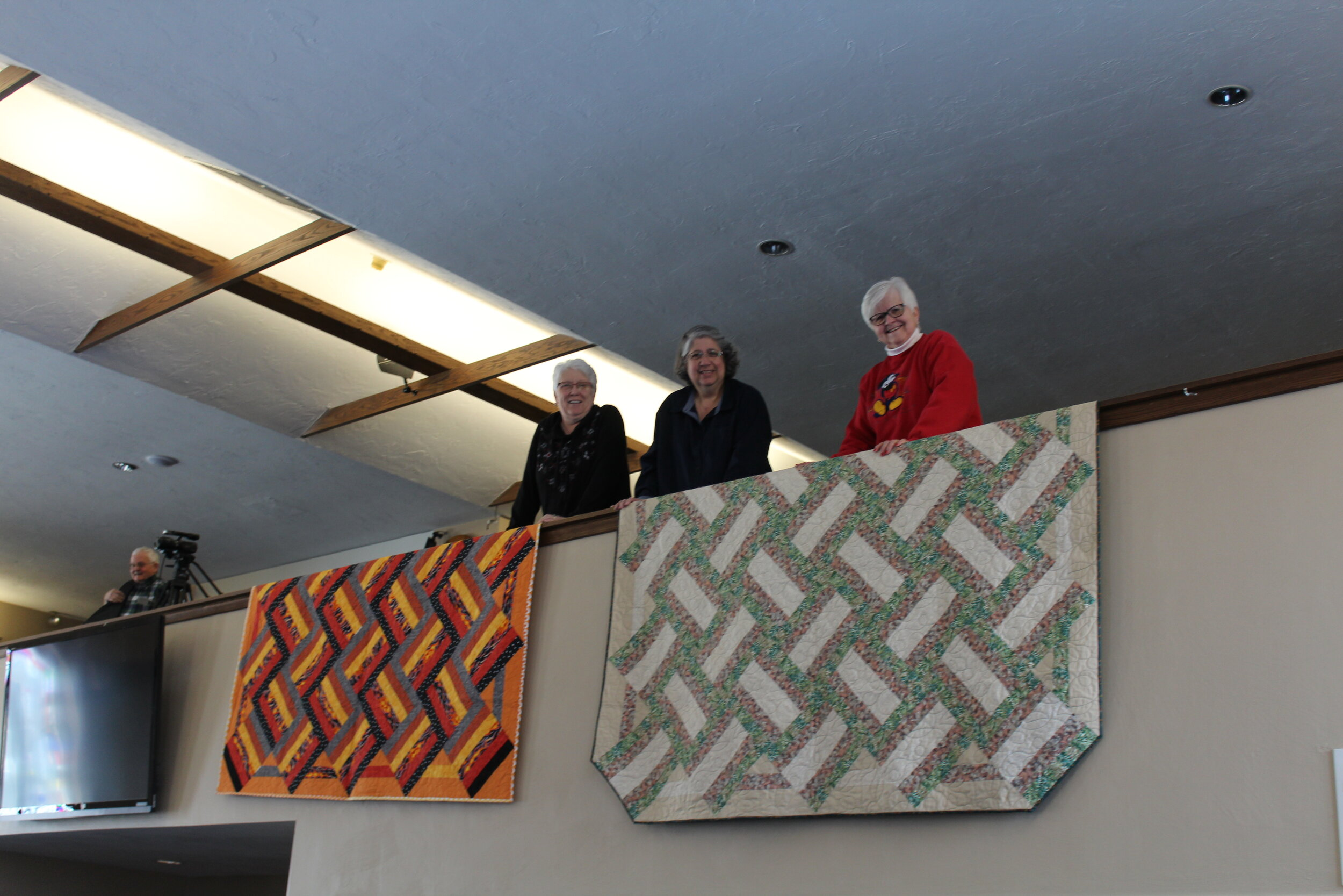 Jan Andree, Barb Barnett, and Louise Warner display quilts to be blessed at worship services before delivery to the young people at MHY.