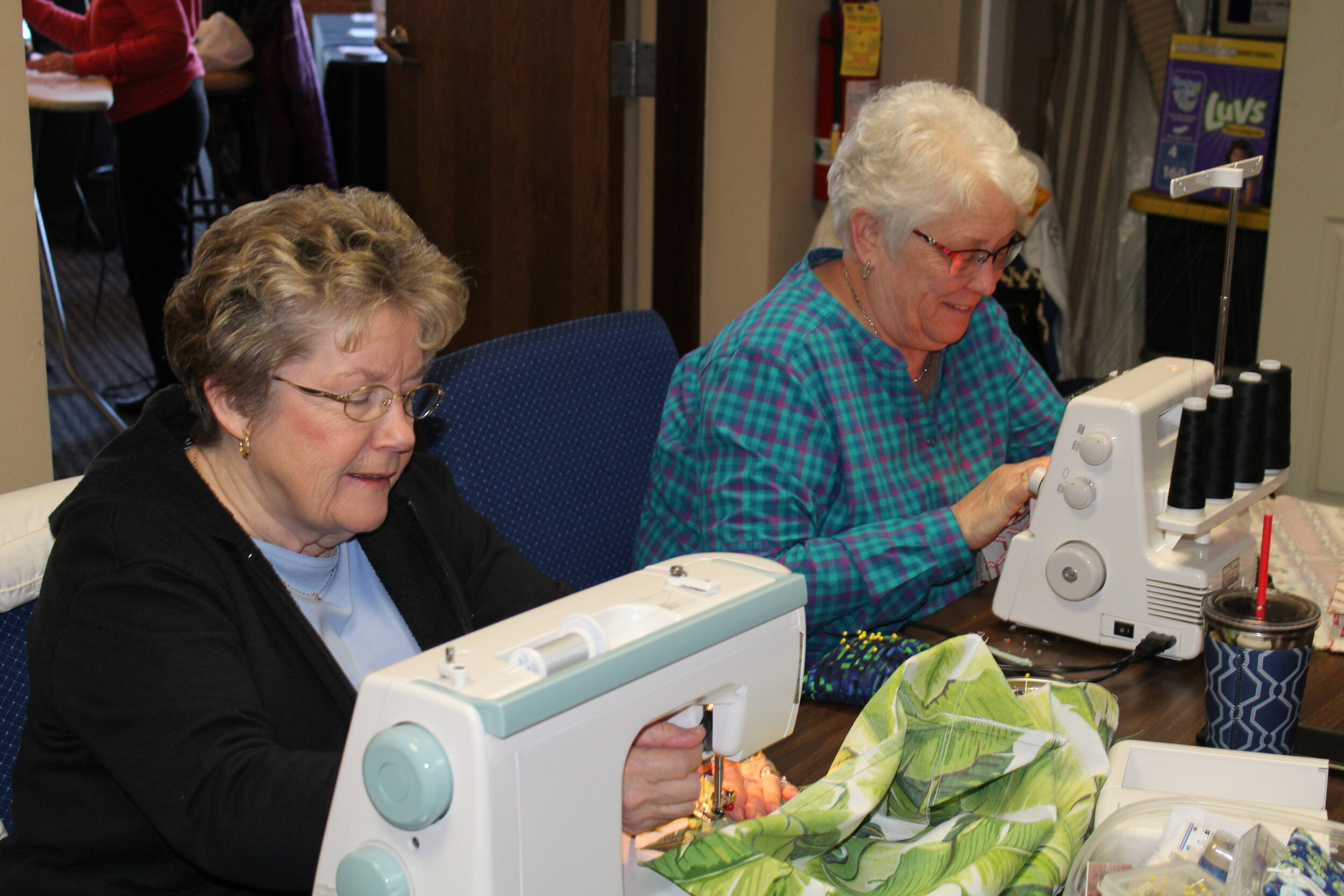 Quilt & More gatherings allow friends to work together on MHY quilts, fabric bags, or any sewing/knitting project they like. Above: Sherry Cameron and Jan Andree are hard at work.