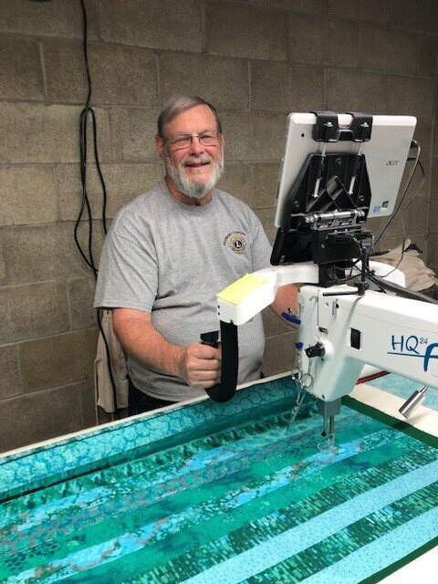 Bud Warner puts all three layers of the quilt together with his long-arm quilting machine.