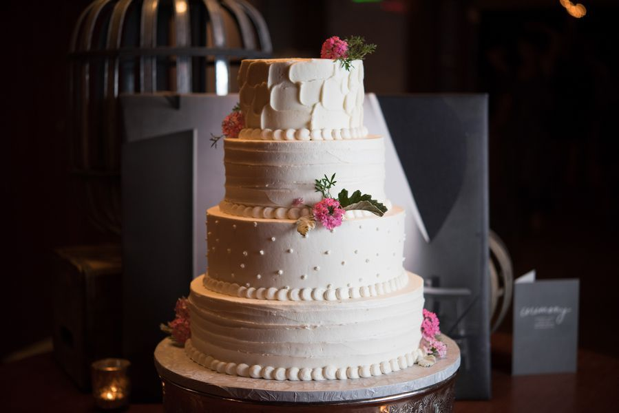 white wedding cake with white patterns and a few small pink flowers