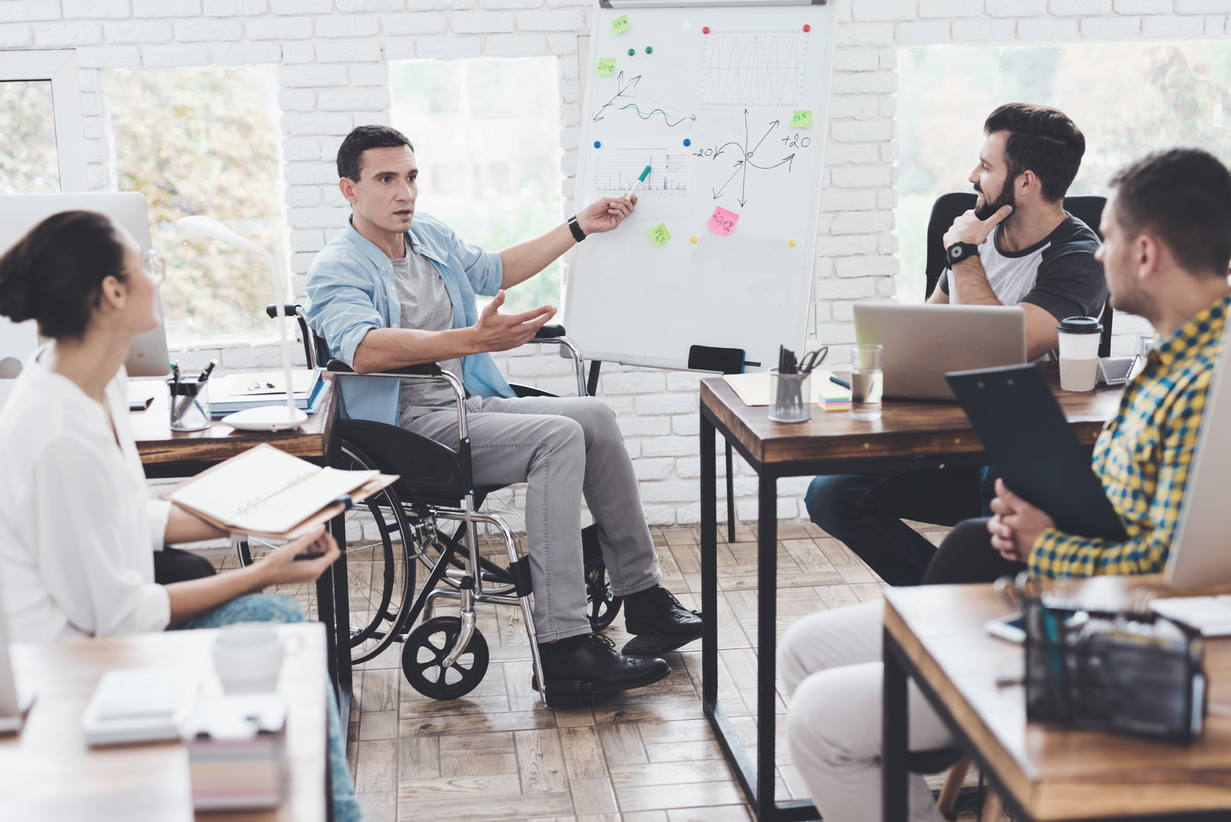 Man in a wheelchair pointing to a whiteboard and discussing graphic drawn on it with colleagues.