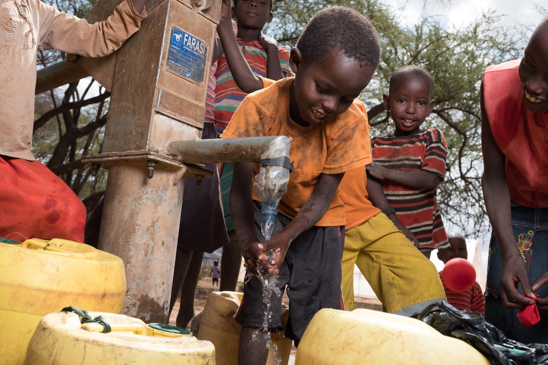 Children playing in water well, Samburu Kenya Africa