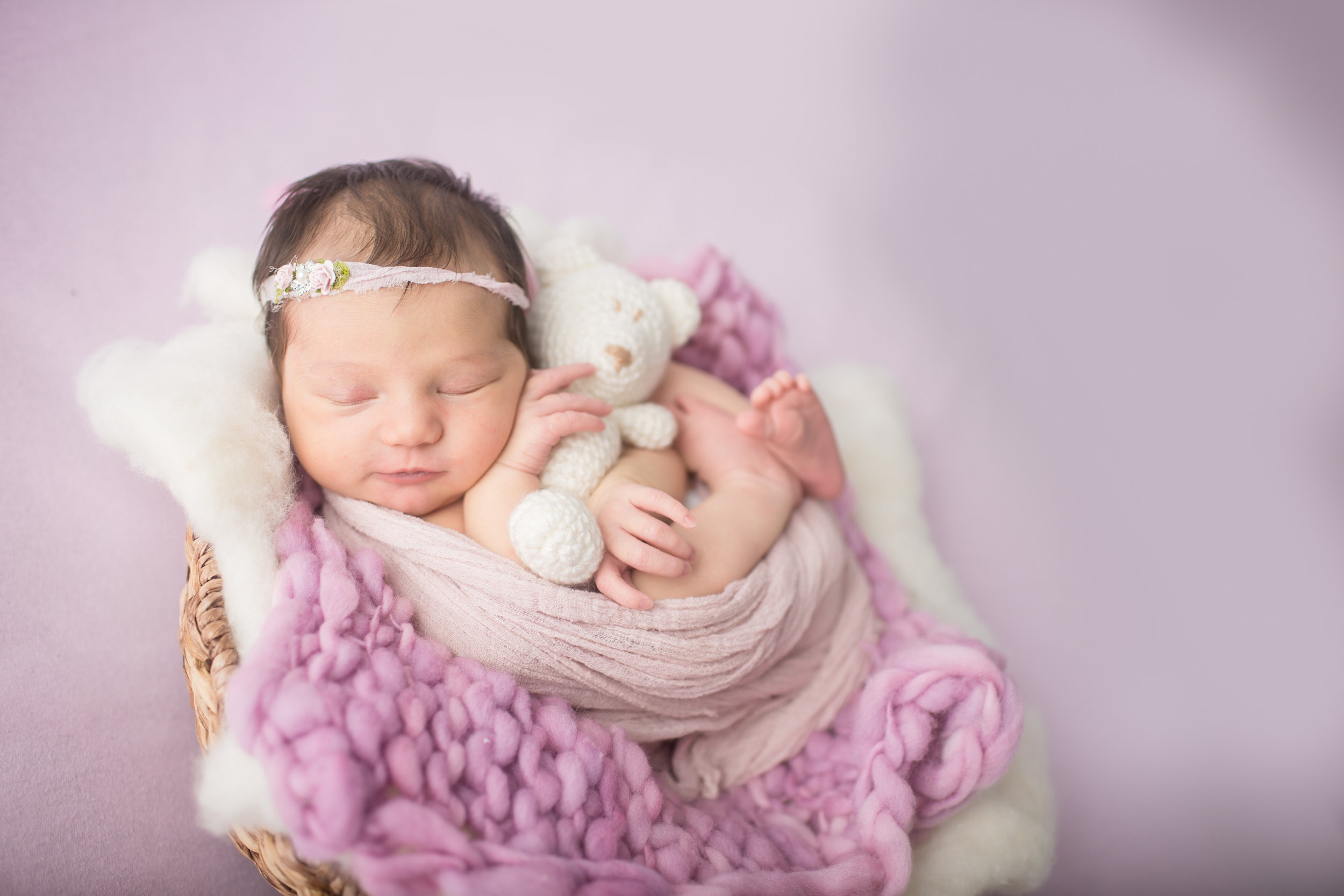 Davison Michigan newborn portrait photographer posing a newborn girl with teddy bear at her studio photo shoot