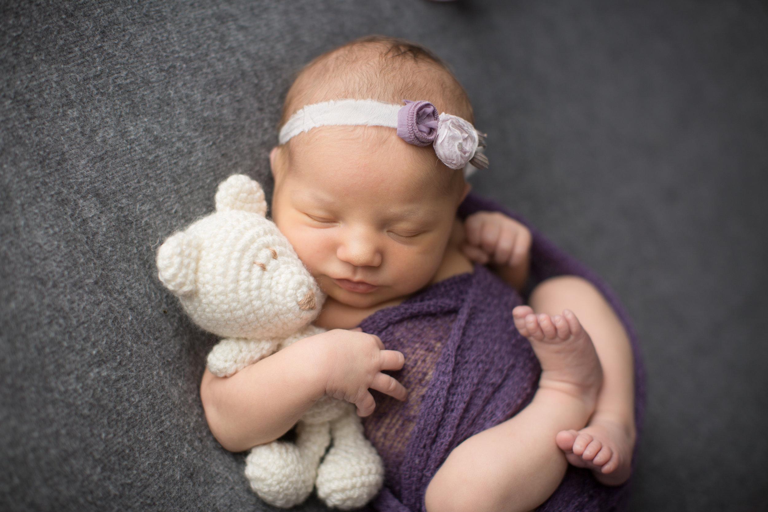 professional portrait of a newborn baby girl holding a teddy bear