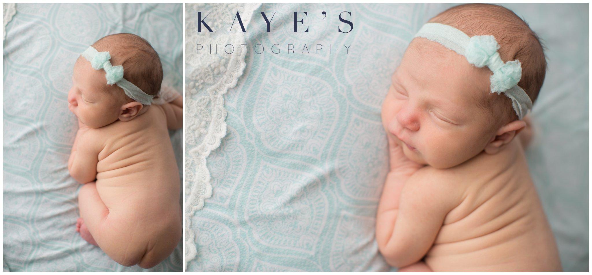 Celebrity newborn girl on blue blanket wearing headband getting in studio photos