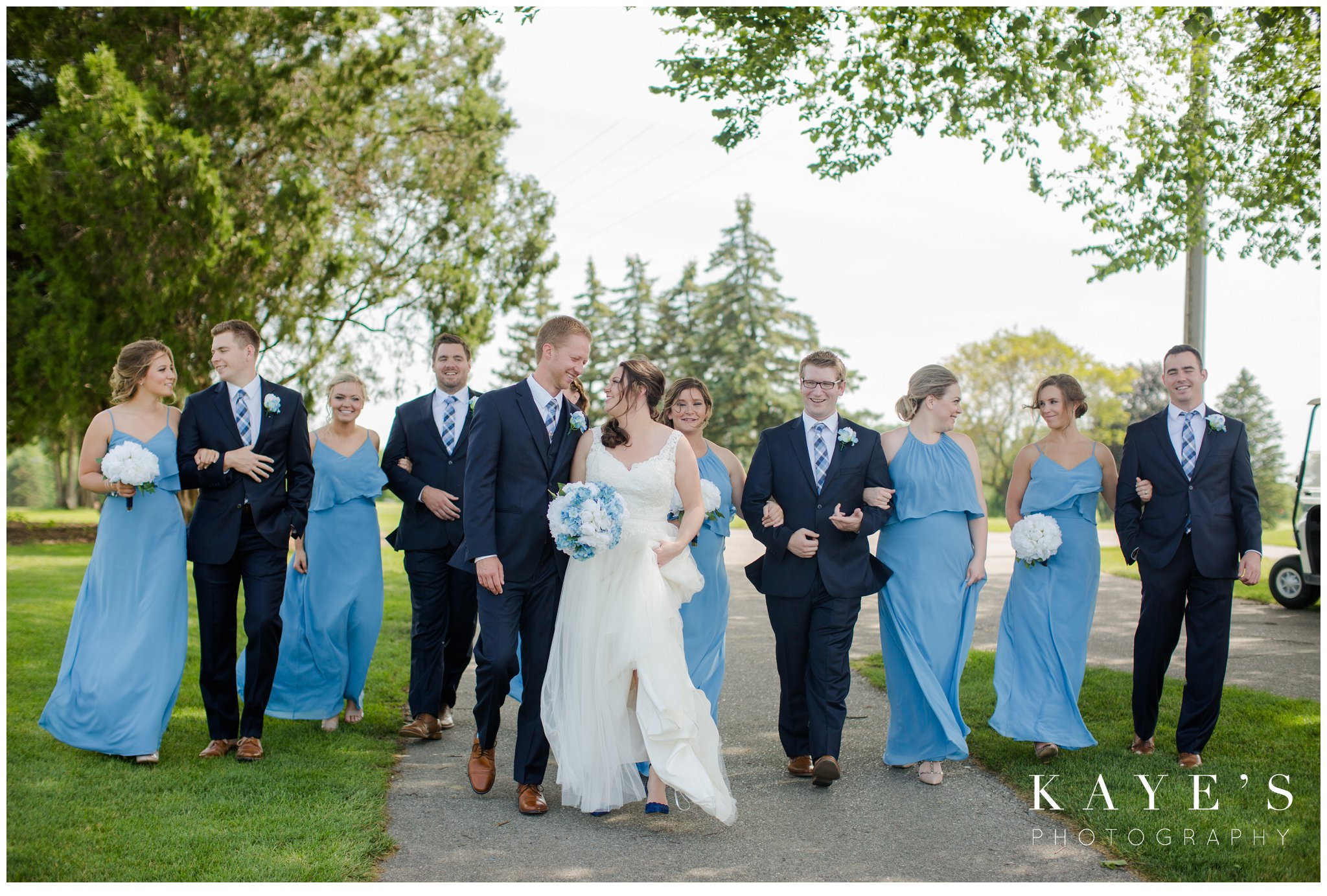 bridal party walking together on golf course and laughing during wedding portraits