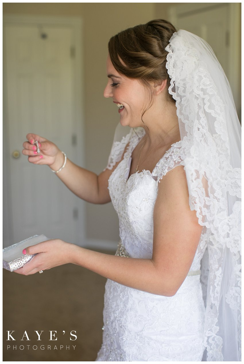 Bride opening her gift from her groom in Flint Michigan during wedding