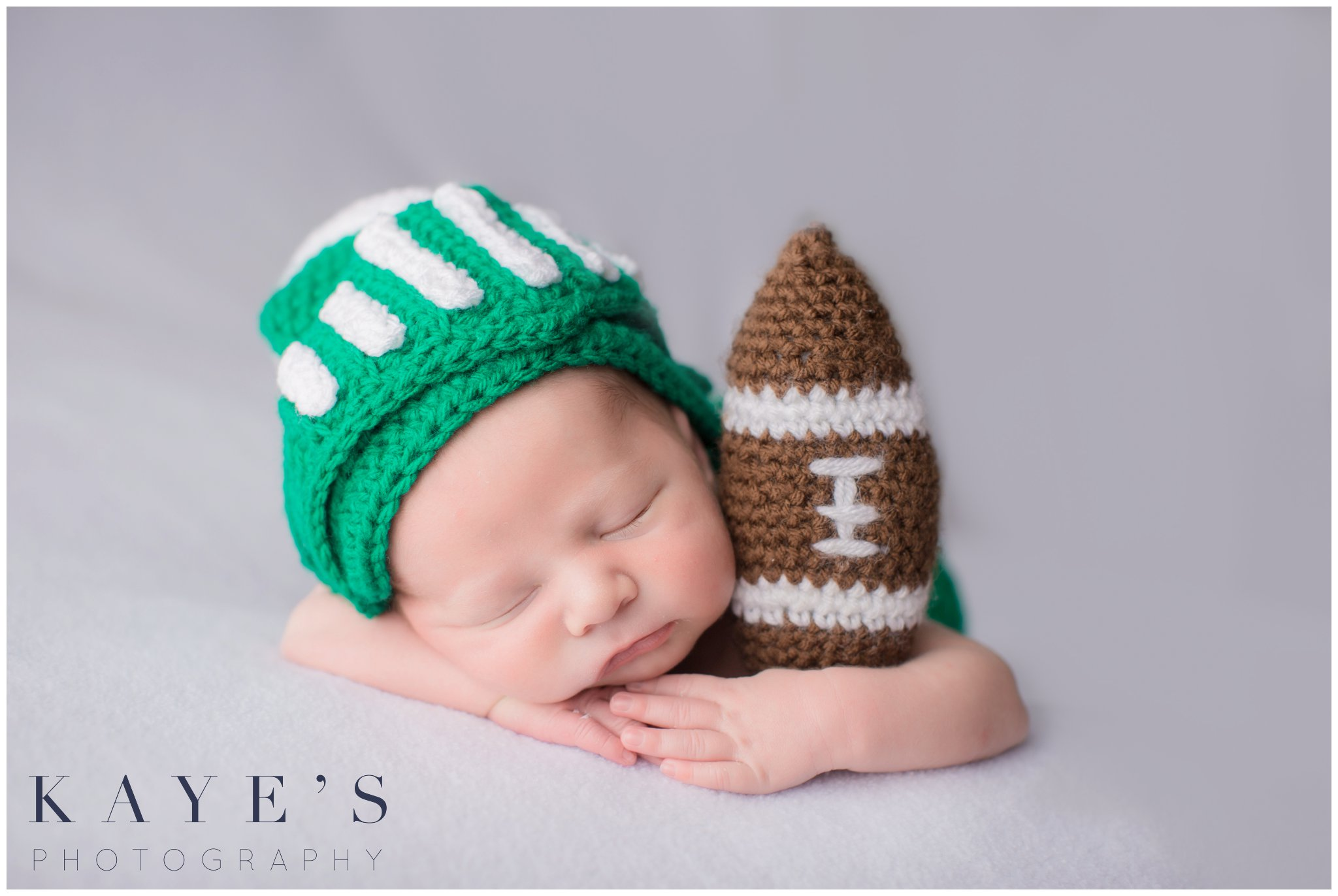 baby boy in michigan state gear holding a knit football