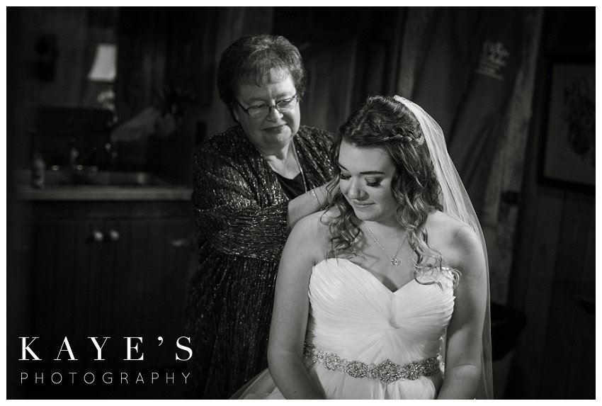 grandmother putting on necklace in bridal suite in ann arbor michigan at misty farms