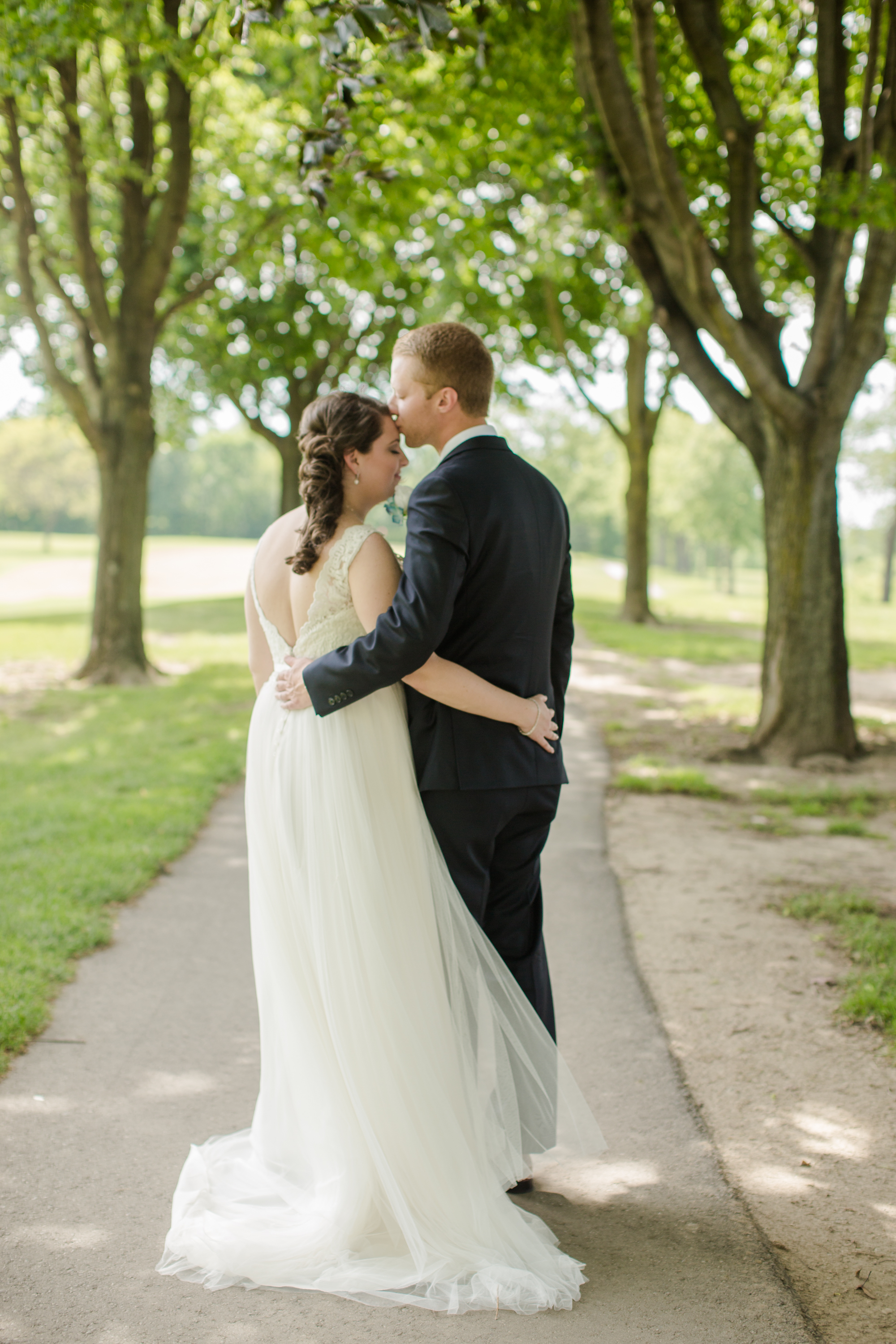 groom kissing bride on forehead during wedding photos in Rochester Michigan