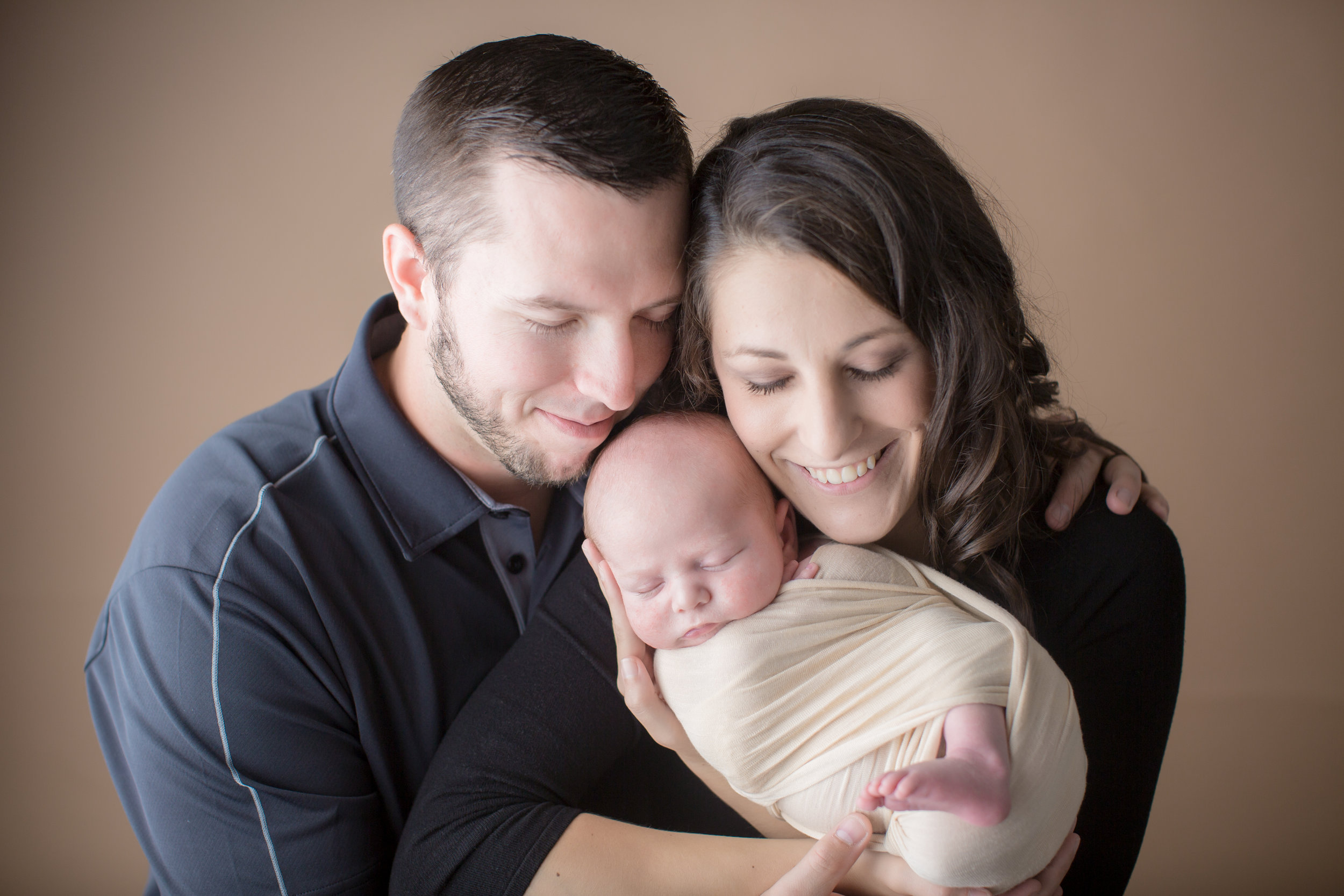 parents holding newborn baby while taking baby pictures