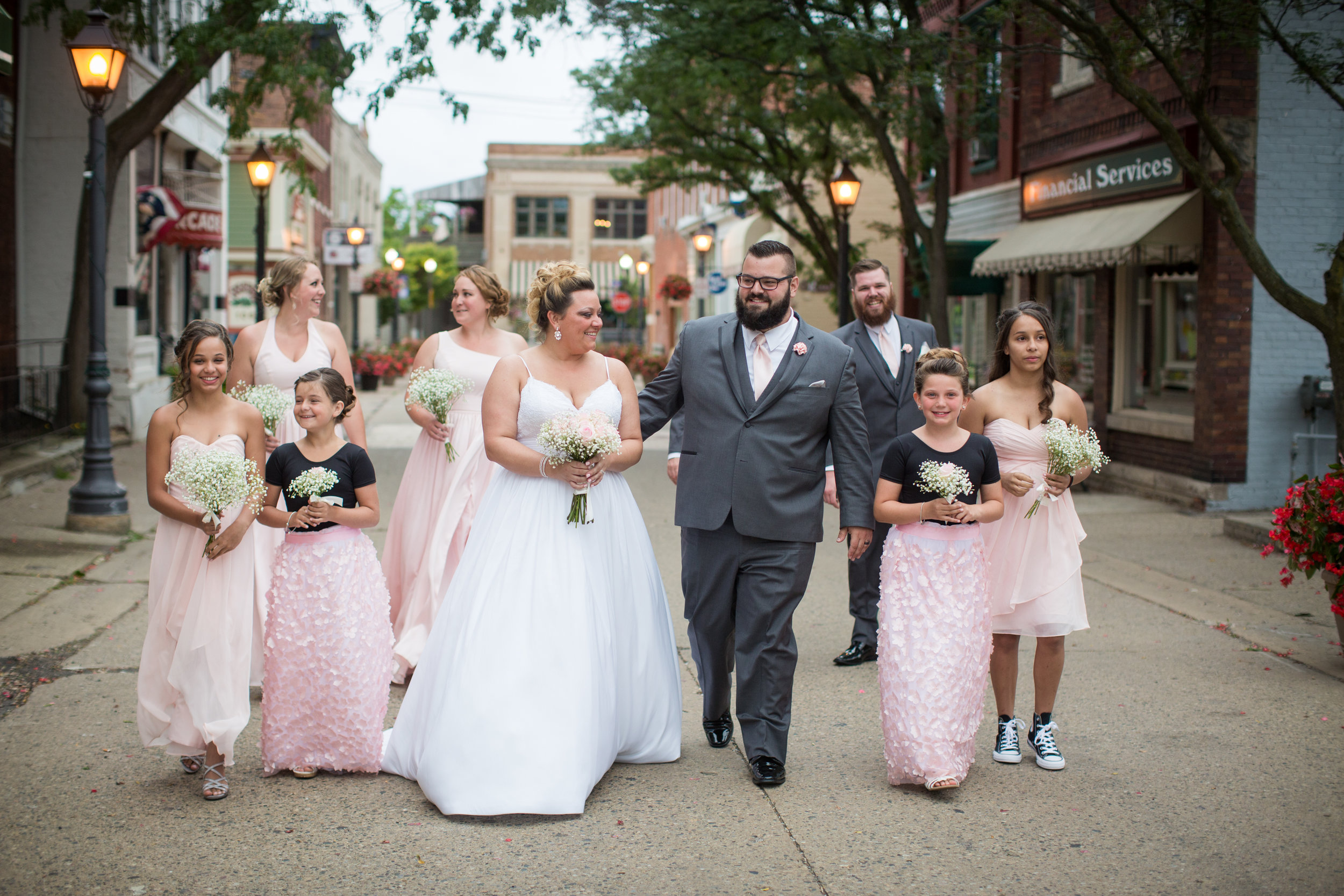 Bride and groom walking down street during wedding pictures in Rochester Michigan
