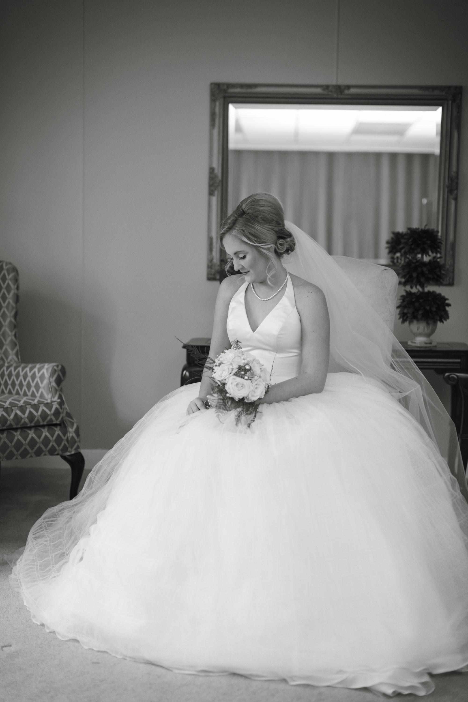 Bride sitting in chair taking wedding photos with Detroit wedding photographer