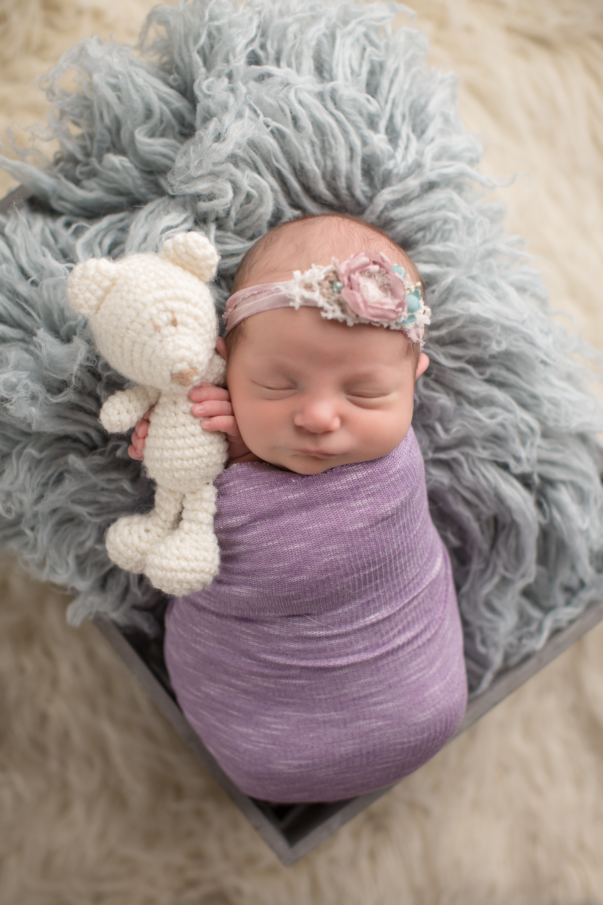 newborn baby girl wrapped up in blanket snuggling with bear during baby photos