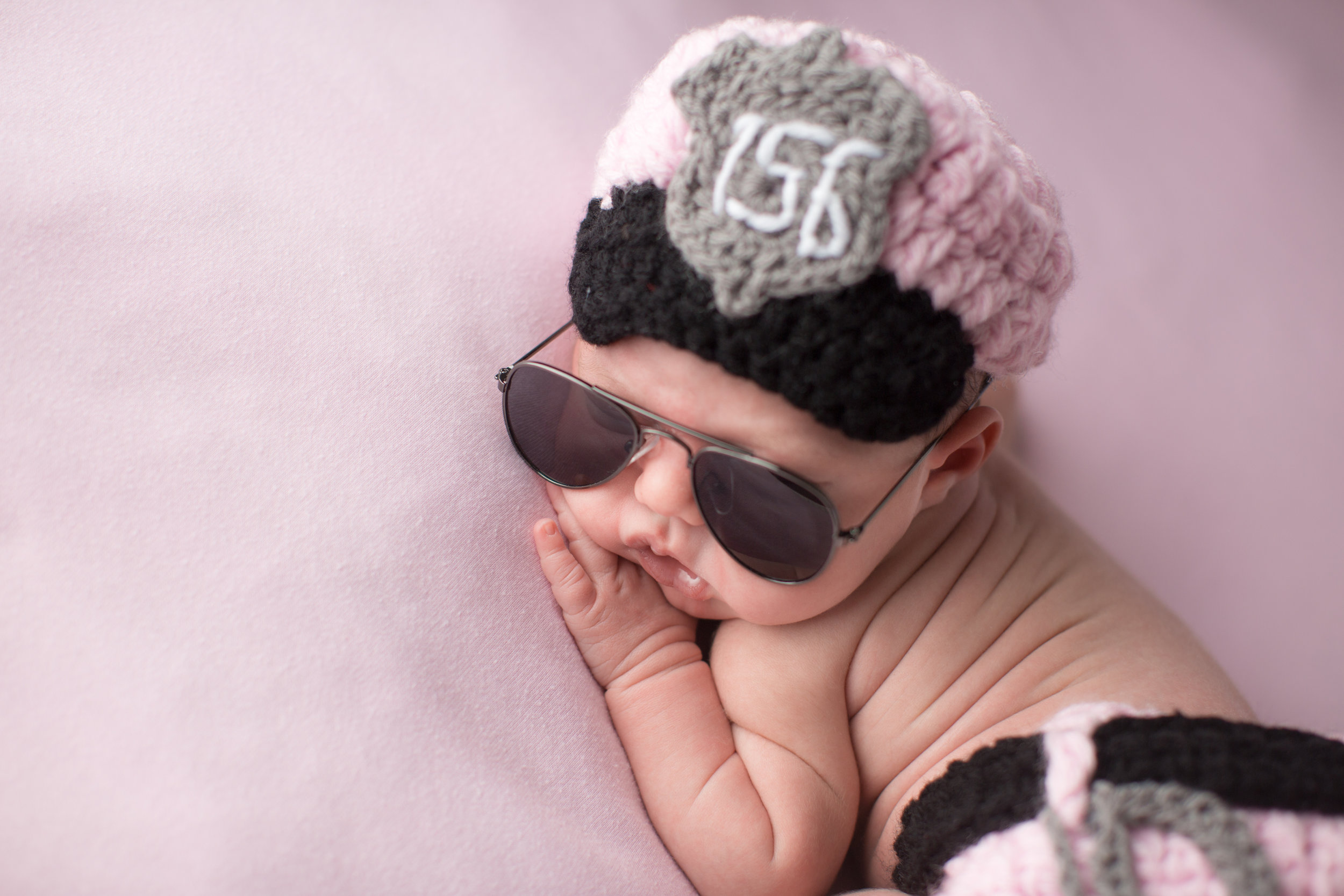 baby girl wearing police uniform and sunglasses during newborn photos in flint Michigan