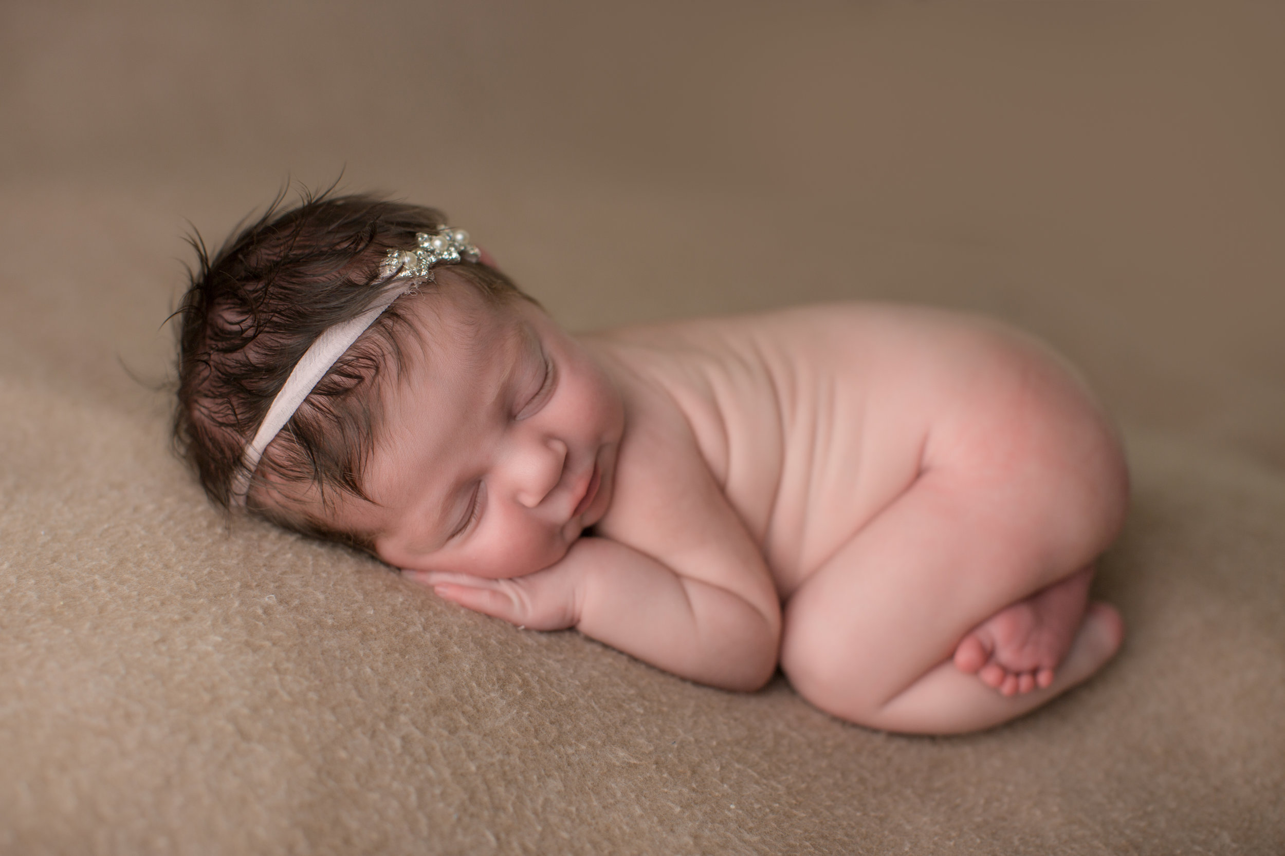 Newborn baby posing during baby photos in Flint Michigan