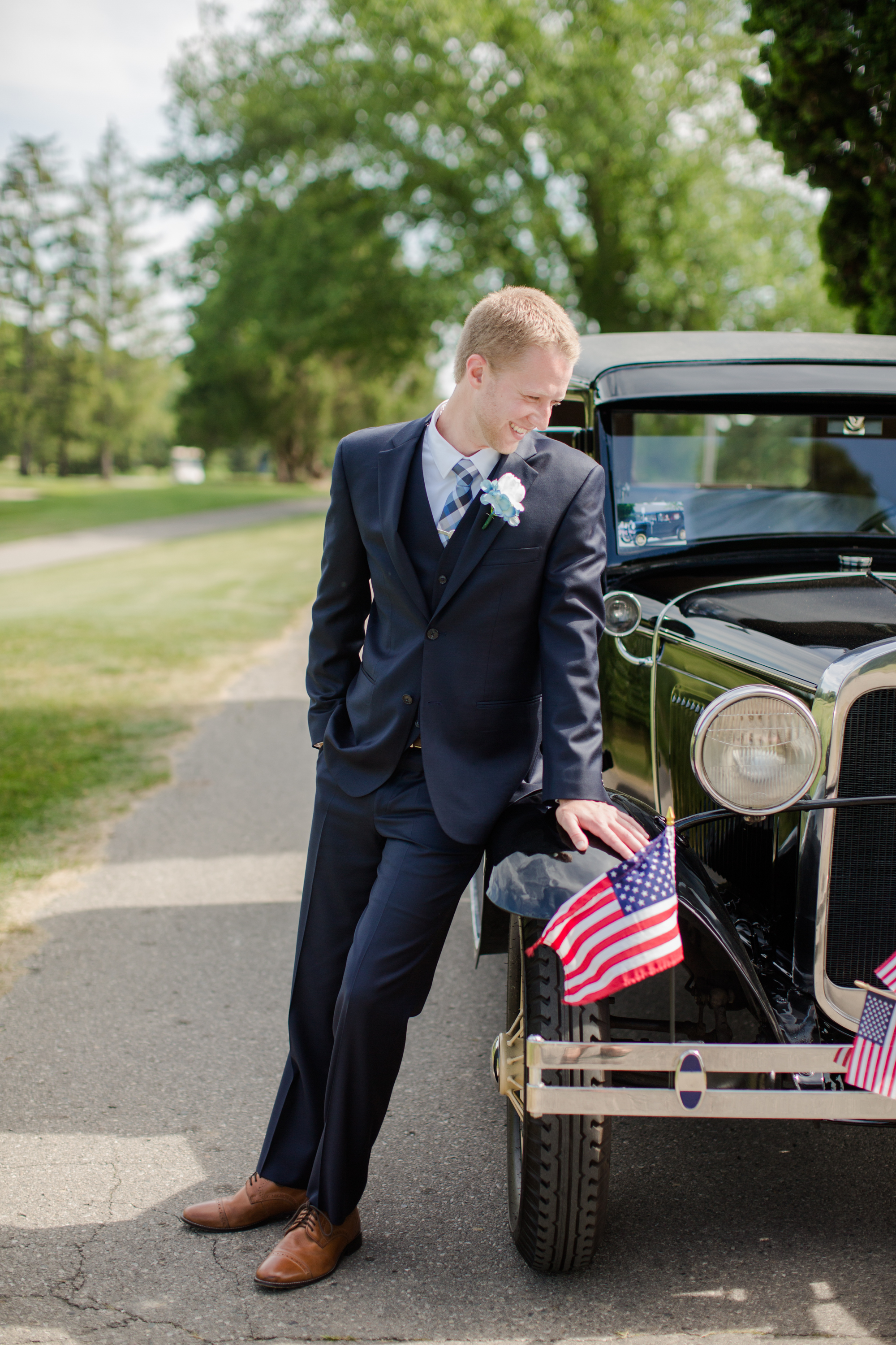 detroit michigan groom leaning against a car for wedding photos