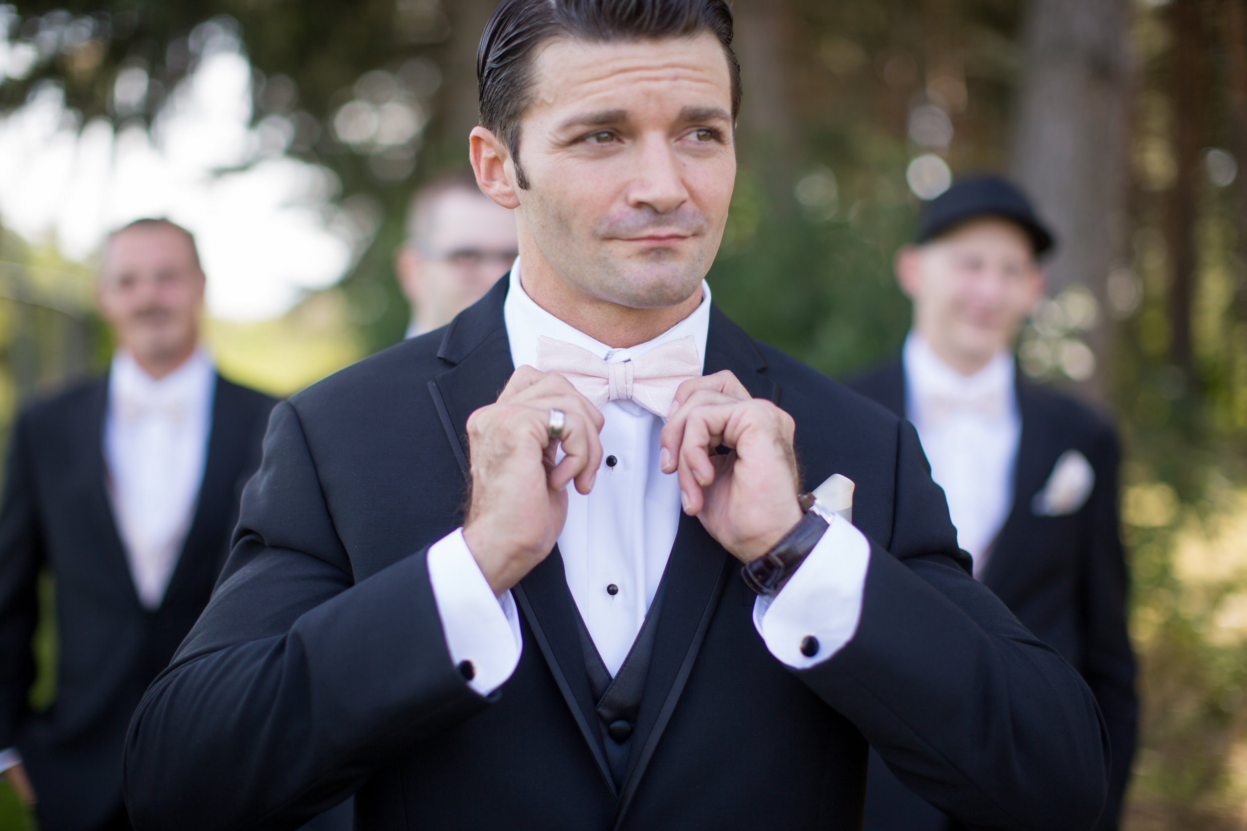 groom posing for wedding pictures while doing up his bowtie in rochester michigan