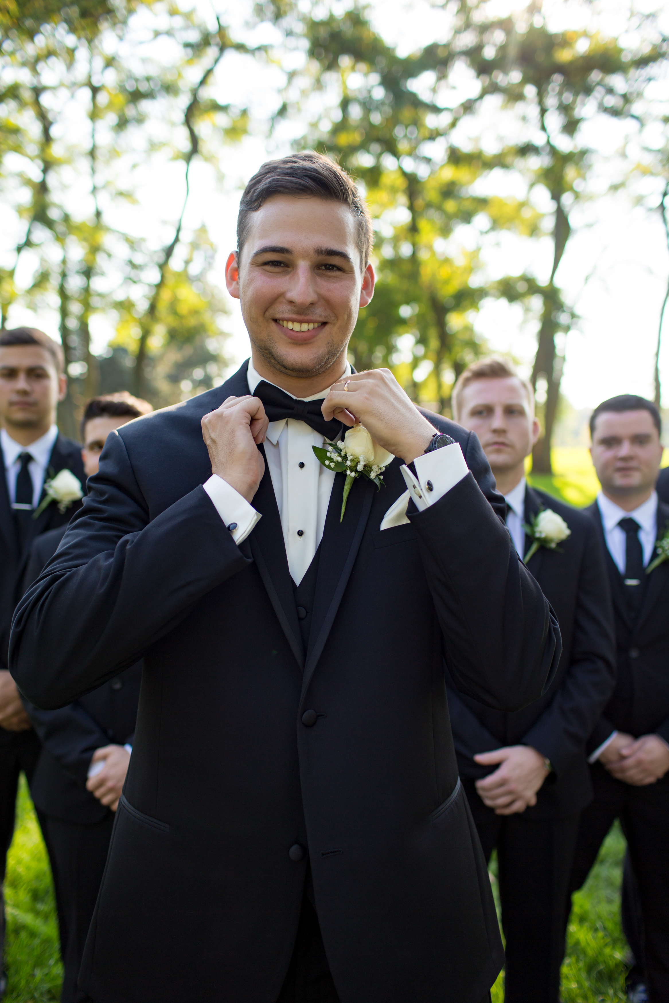 Groom getting for wedding photos with his groomsmen in detroit michigan