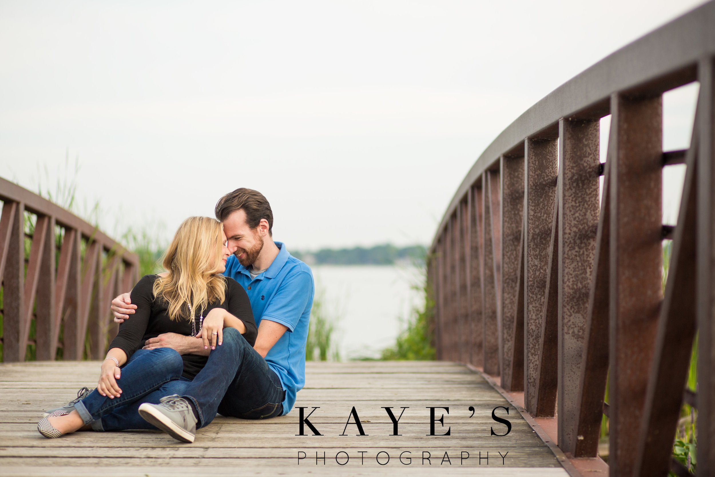 couple cuddling on bridge for professional engagement photos